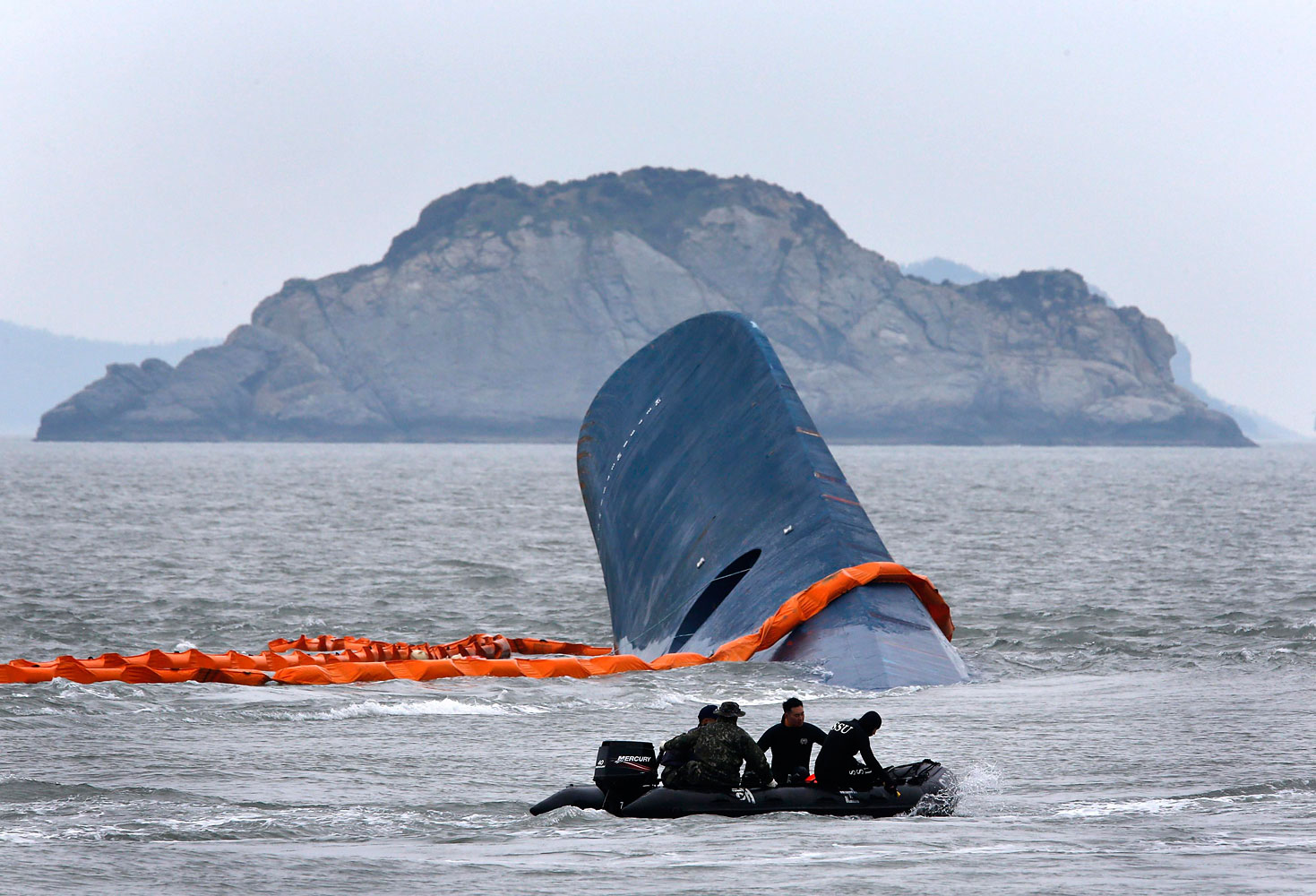 A vessel involved in salvage operations passes near the upturned South Korean ferry Sewol in the sea off Jindo April 17, 2014.