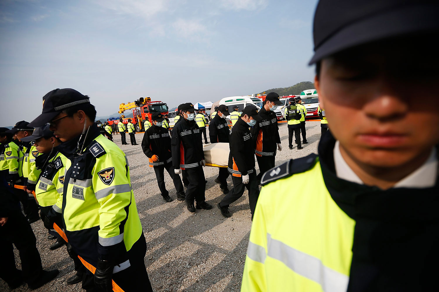 Rescue workers carry the body of a passenger who was on the capsized Sewol passenger ship in Jindo, the South Korean port town where family members of the missing passengers have gathered, on  April 20, 2014
