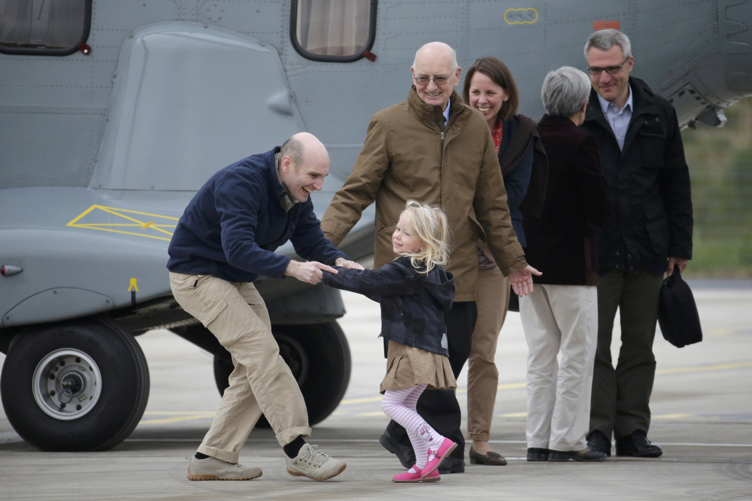Nicolas Henin (L), former French hostage and journalist, is greeted by his family moments after a transfer by helicopter from Evreux to the military airbase in Villacoublay, near Paris, April 20, 2014.
