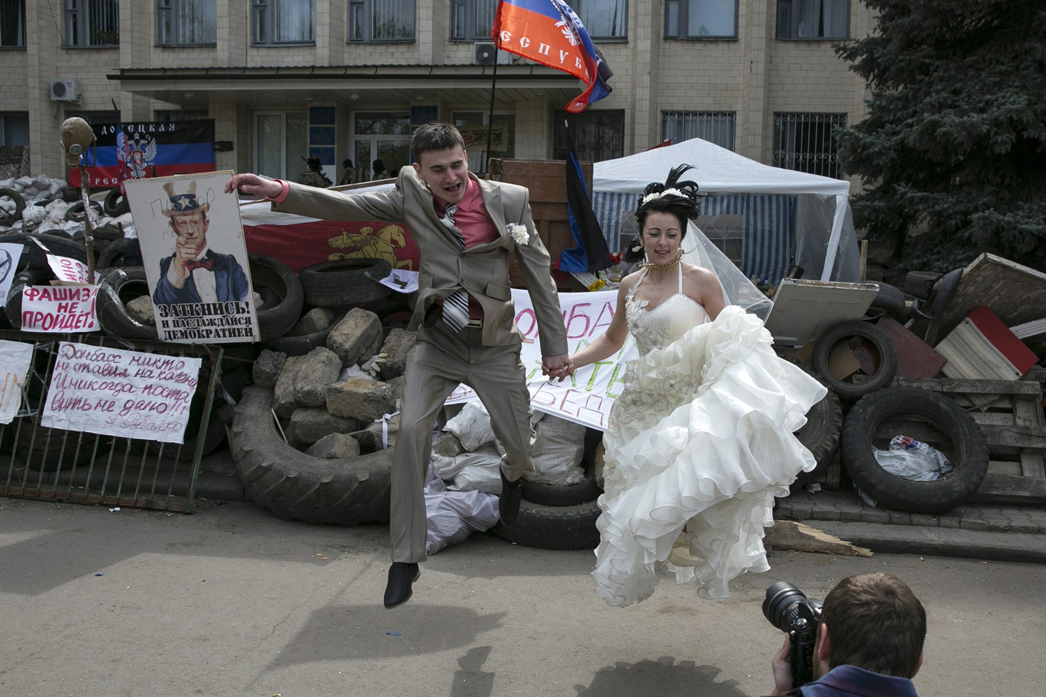 A bride and groom jump for a picture in front of barricades outside a regional government building seized by pro-Russian armed men in Kramatorsk, eastern Ukraine, on April 22, 2014.