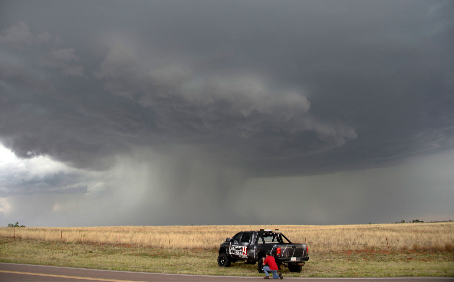 A storm chaser photographer looks at thunderstorms supercells passing through areas in Vinson, Oklahoma late April 23, 2014. The thunder storms on were a precursor of what's forecast for this coming weekend.
