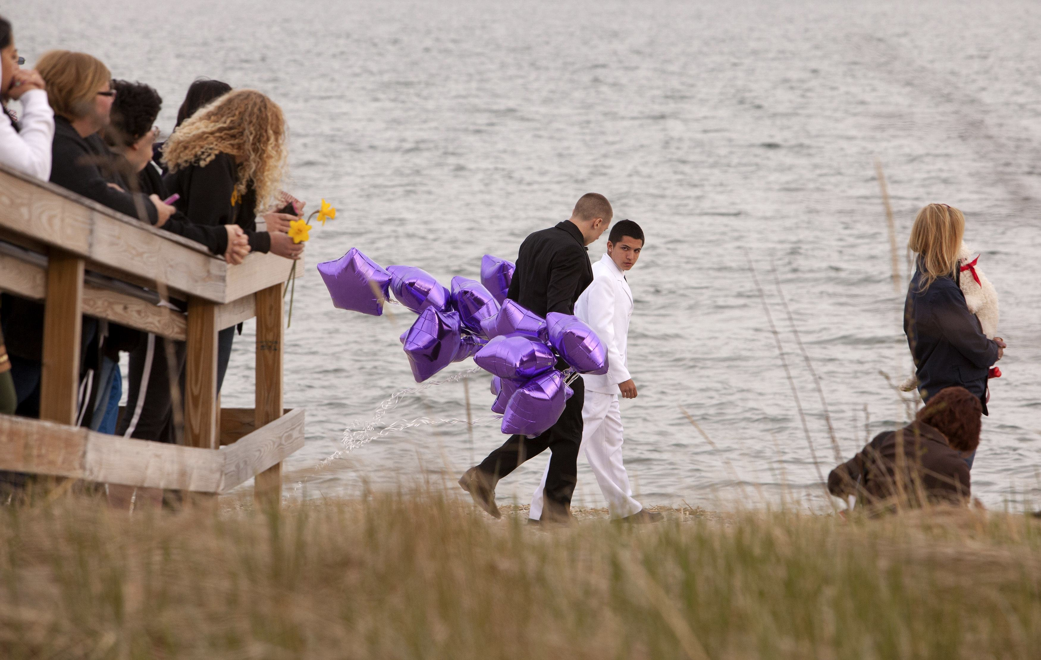 Students arrive at the beach for a vigil in honor of slain student Maren Sanchez wearing their prom clothes carrying balloons in Milford, Conn. April 25, 2014.
