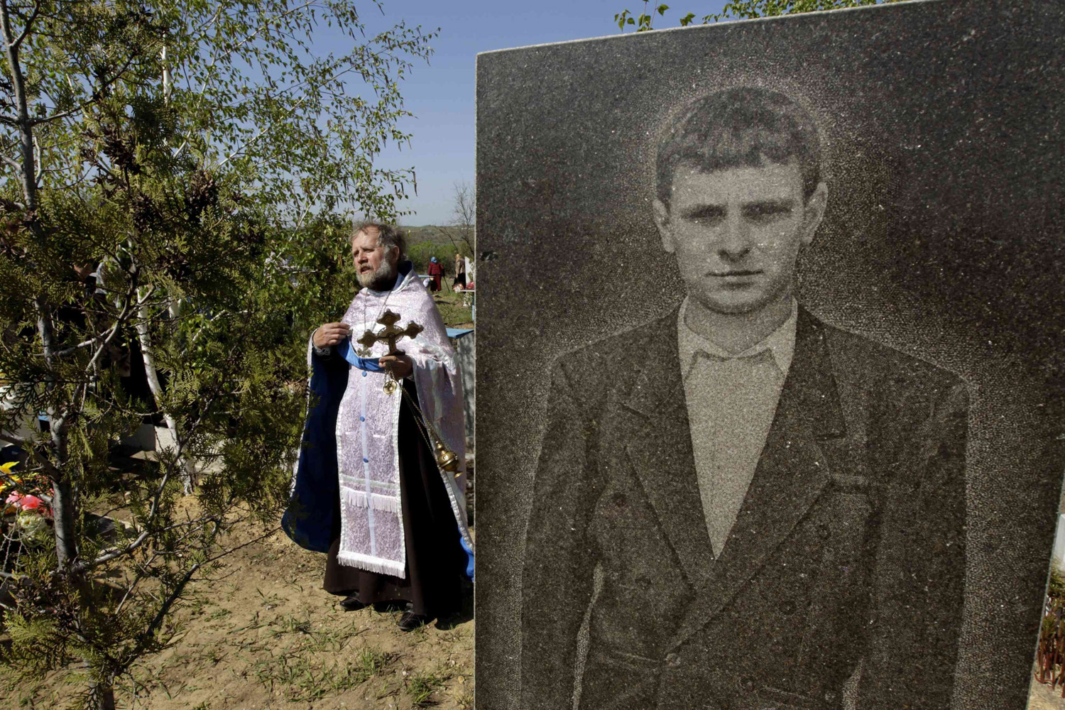 Apr. 27, 2014. An Orthodox priest walks past a portrait of a man on a grave, as he conducts a service in a cemetery near the village of Zimogorie, on the outskirts of Luhansk, eastern Ukraine.