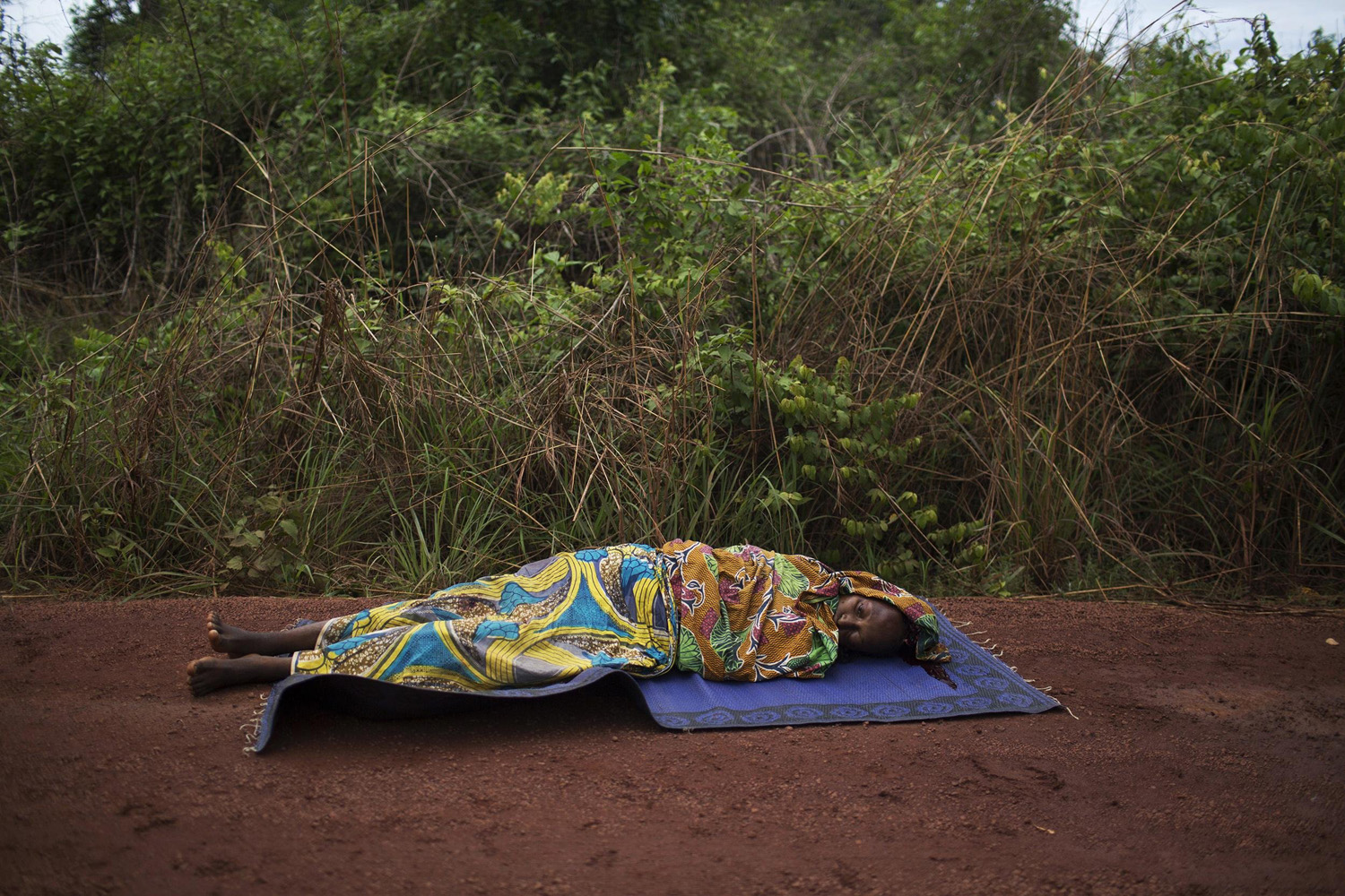 Apr. 28, 2014. A woman lies on the road dying from a gunshot wound to the head close to the village of Dekoua after the armed peacekeeping convoy from the African Union operation in CAR (MISCA) she was travelling in came under attack by anti Balaka militiamen.