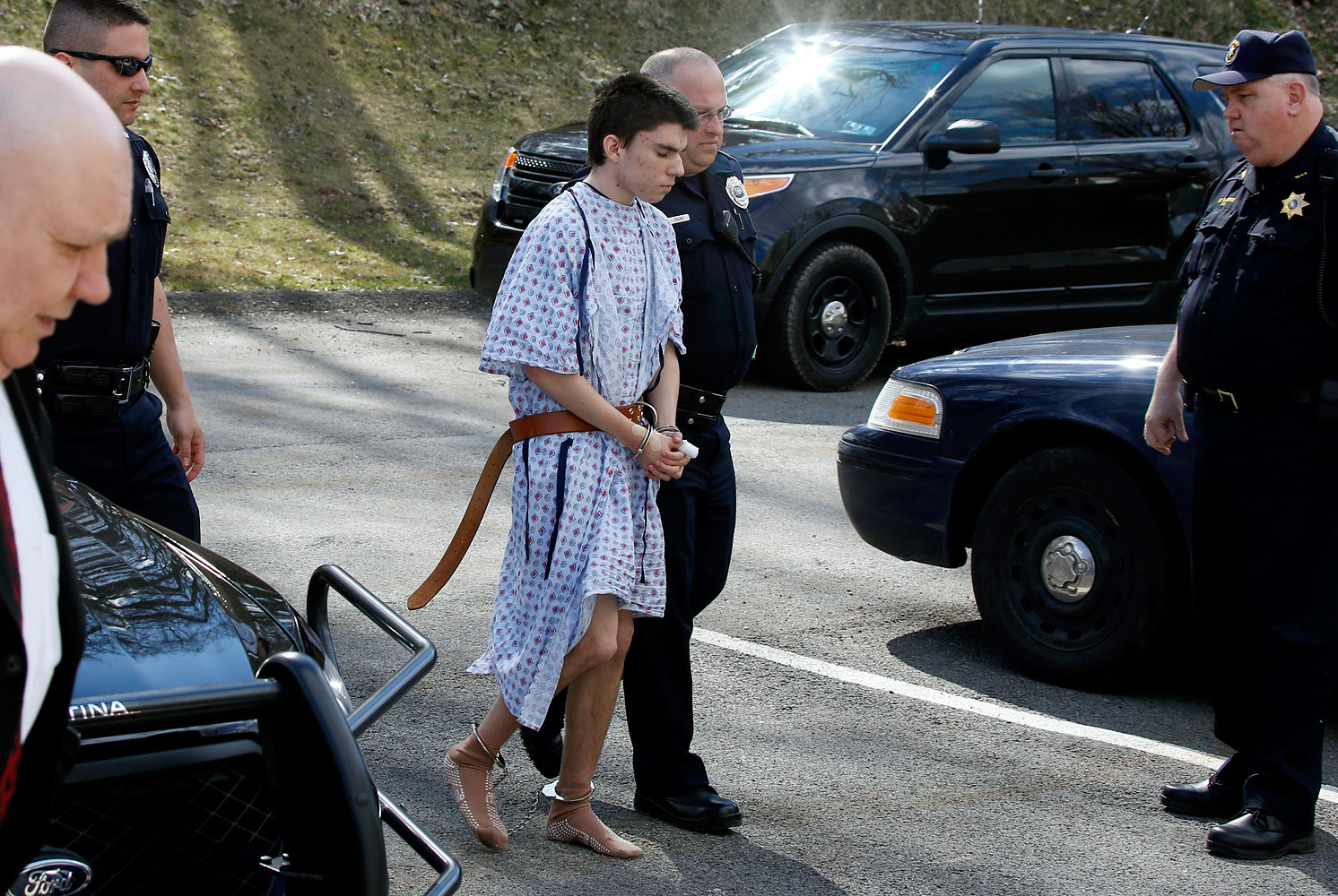 Alex Hribal escorted by police to a district magistrate to be arraigned, April 9, 2014, in Export, Pa.