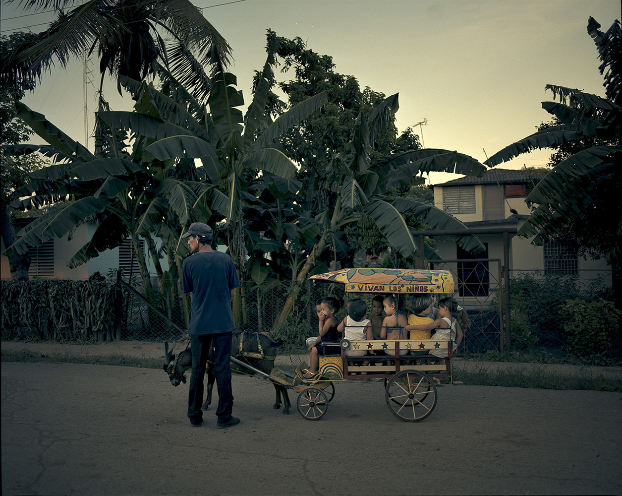An old man drives his cart, which is pulled by a male goat and full of children in Manati town. A ride around the block costs 1 Cuban peso, or 5 cents of a dollar.