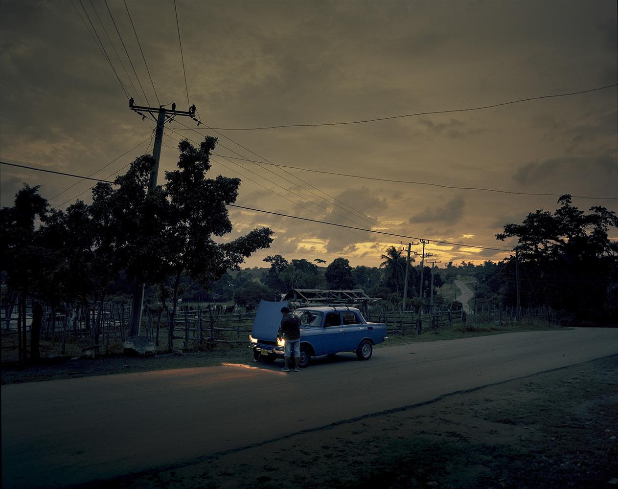 A man repairs car at dusk in the town El Brujo.