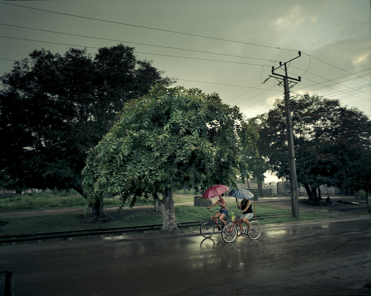 Girls ride their bikes under the rain in Manati town, some 460 miles east  of Havana. Bikes are the main transportation means in this area, due to lack of public transportation.