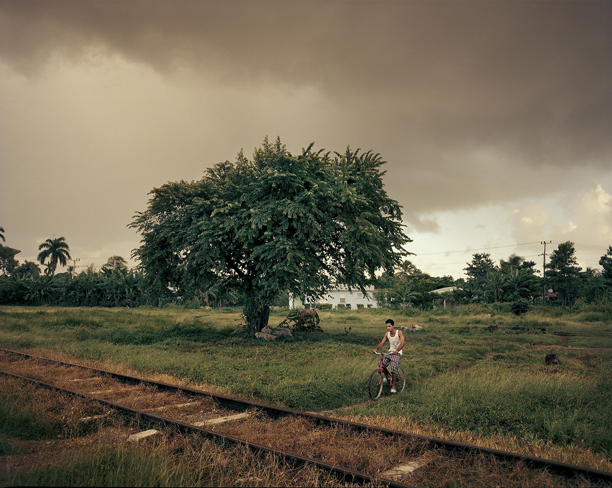 A woman crosses over the railroad in the town Manati.