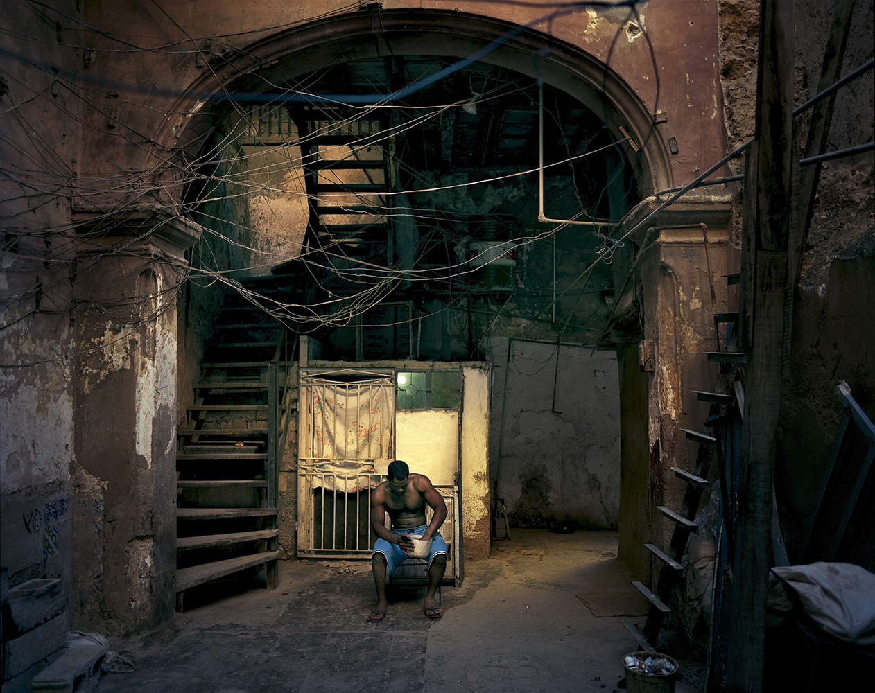 A man sits in an Old Havana tenement building.