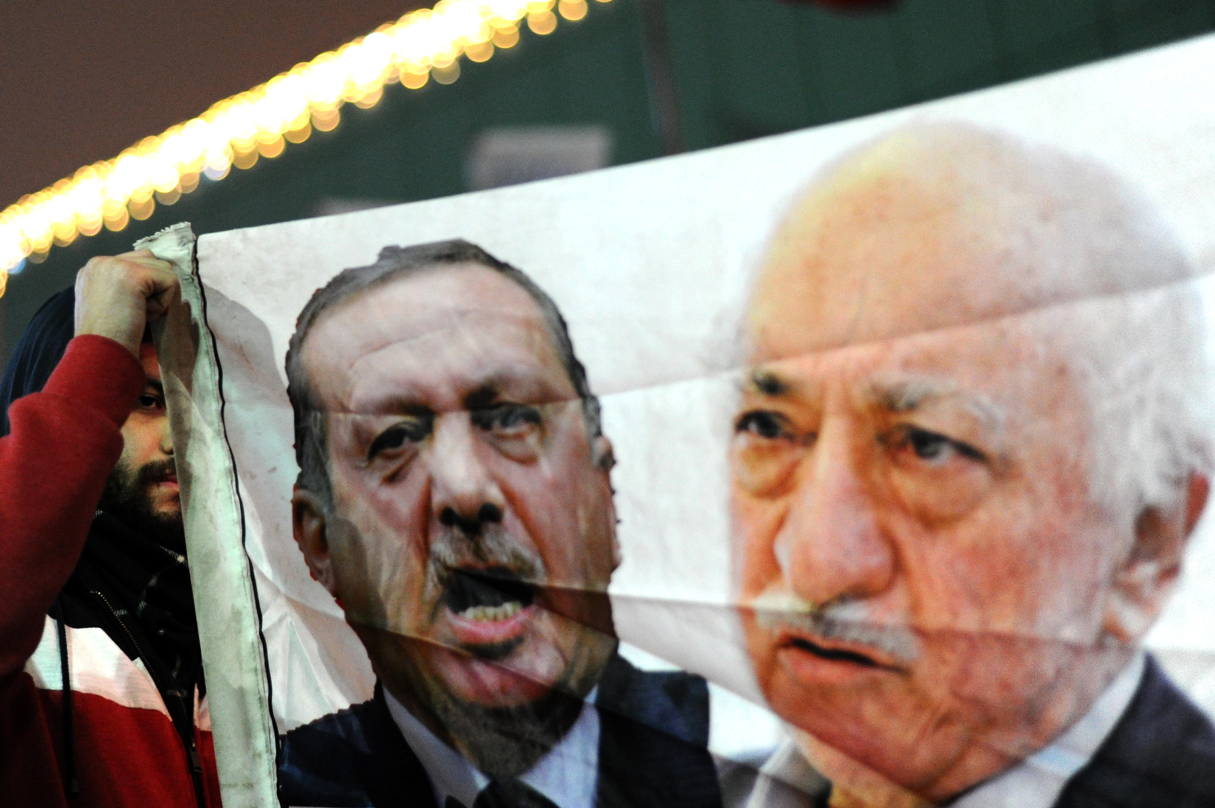 A Turkish protester (L) holds up a banner with pictures of Turkish Prime Minister Recep Tayyip Erdogan (C) and the United States-based Turkish cleric Fethullah Gulen (R) during a demonstration against goverment on December 30, 2013 in Istanbul.