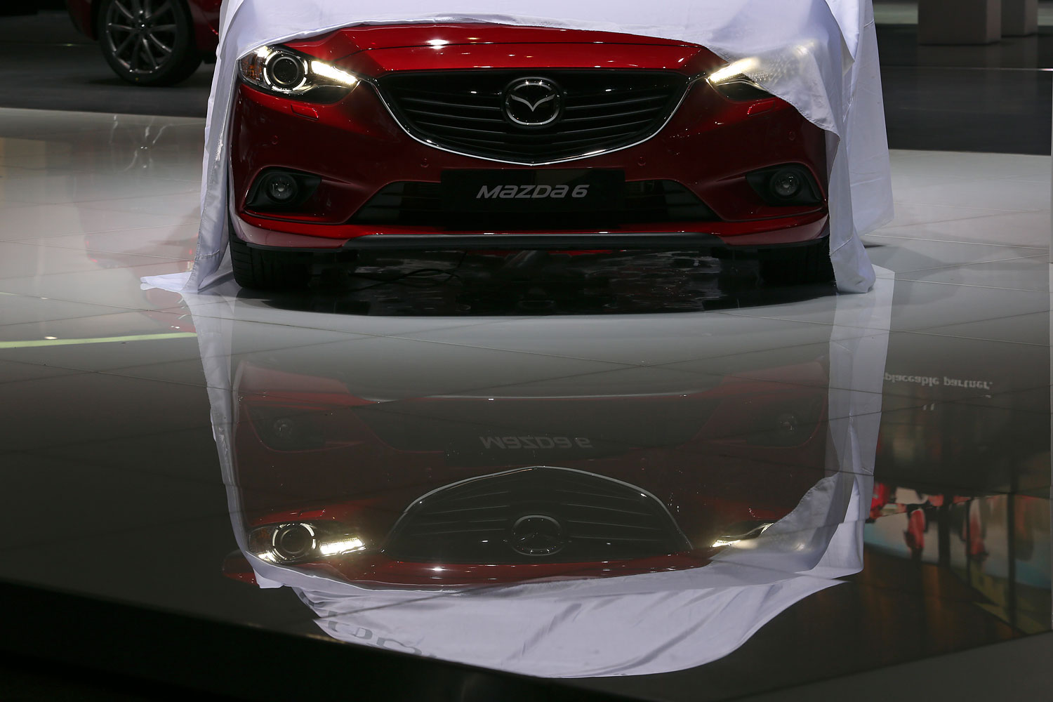 The front grille and bumper of a red Mazda 6 automobile, produced by Mazda Motor Corp., is reflected in the floor of the company's stand ahead of the opening day of the 84th Geneva International Motor Show in Geneva, March 3, 2014.