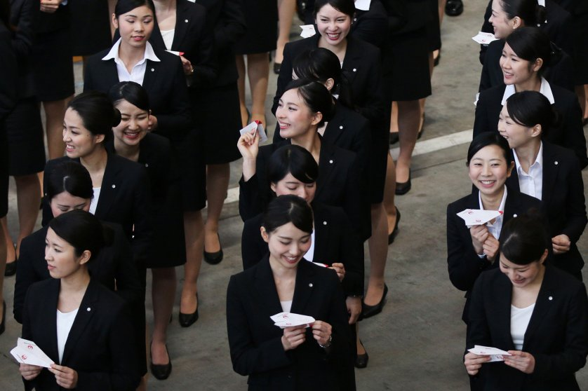 New employees to Japan Airlines Company prepare to release paper planes during a welcoming ceremony at the company's hangar near Haneda Airport in Tokyo on April 1, 2014.