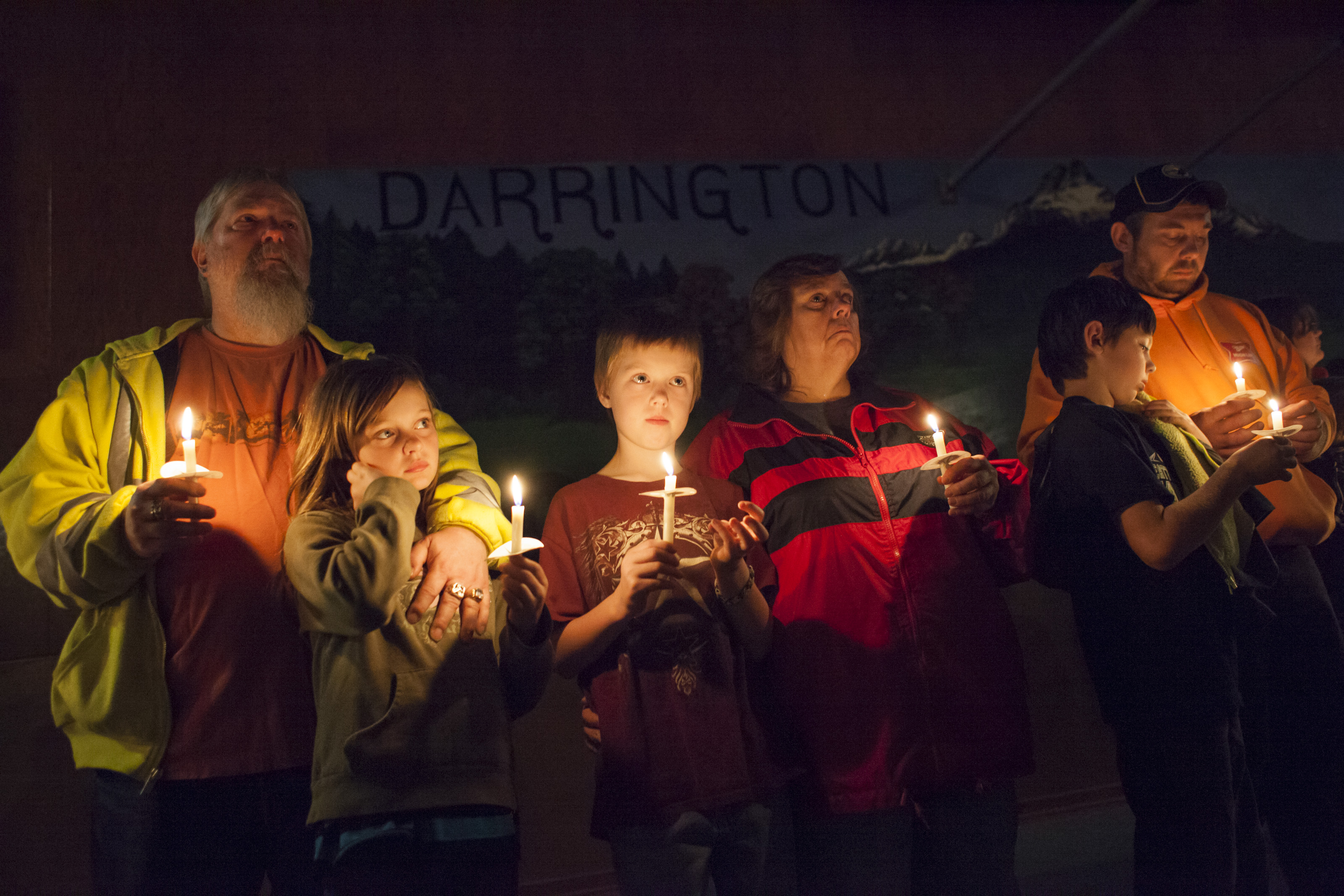 People hold candles during a vigil for mudslide victims at the Darrington Community Center on April 5, 2014 in Darrington, Wa.