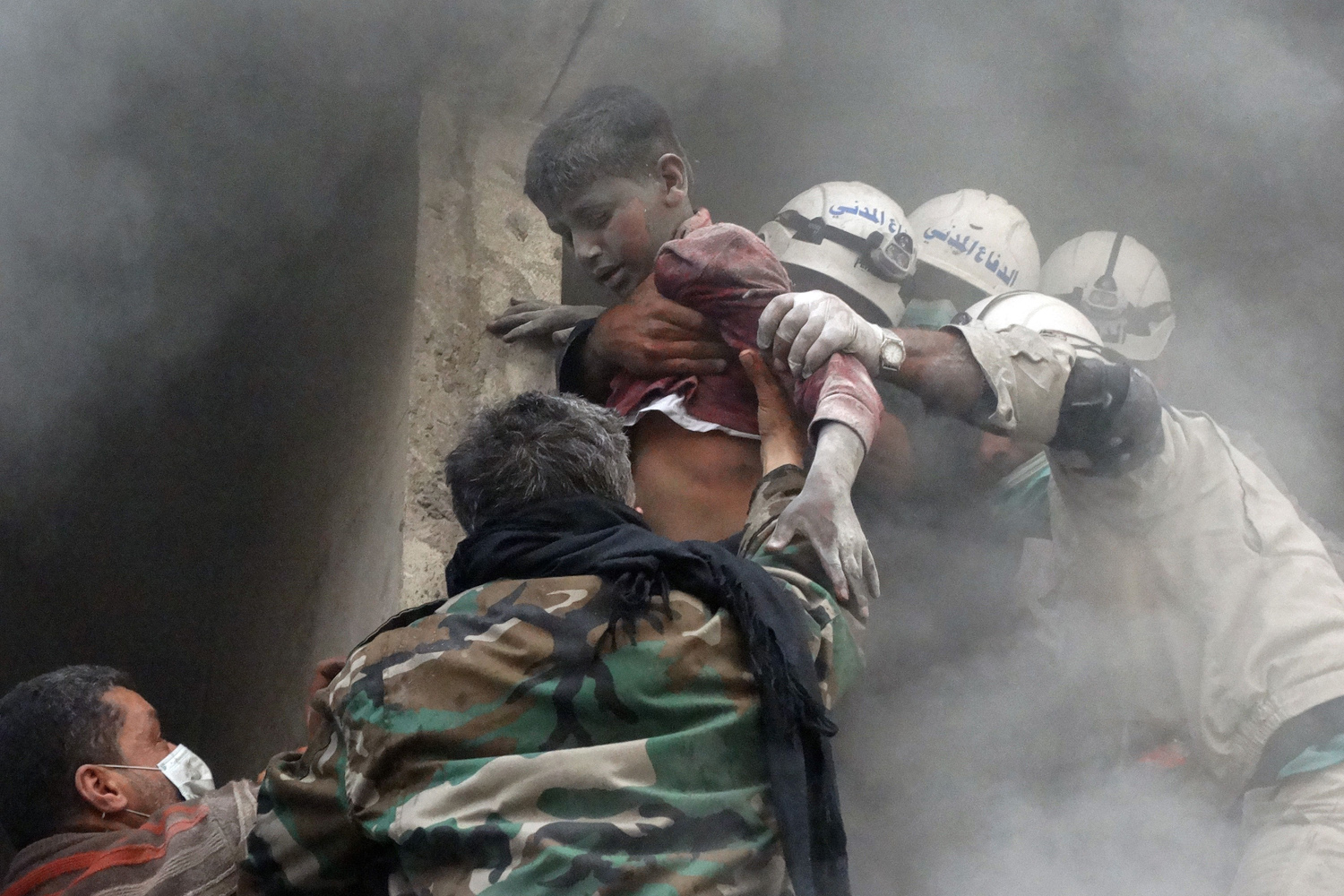Apr. 6, 2014. Emergency responders help evacuate a Syrian boy from a residential building reportedly hit by an explosives-filled barrel dropped by a government forces helicopter in the Shaar neighbourhood of the northern Syrian city of Aleppo.