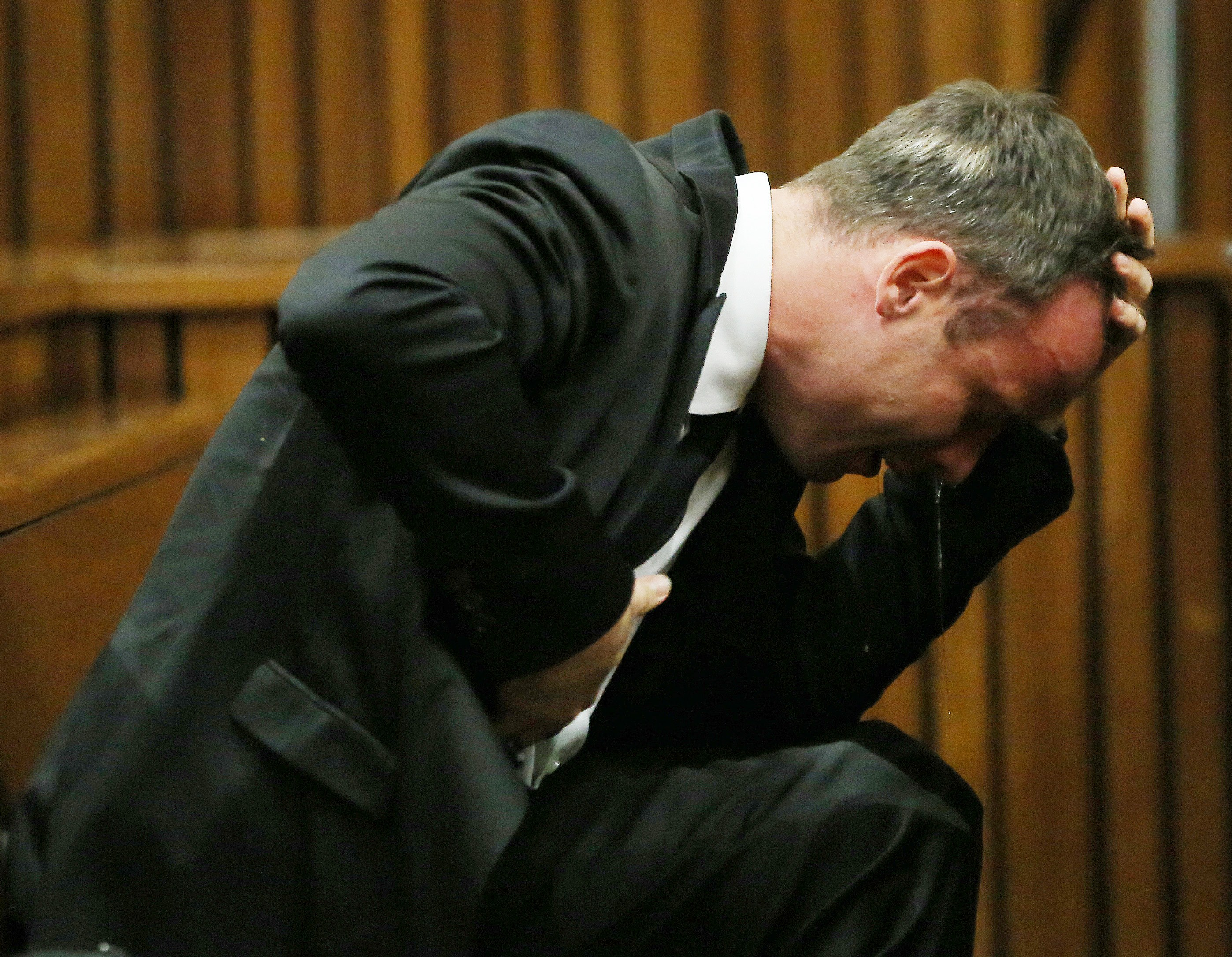 South African Paralympic track star Oscar Pistorius reacts as he listens to evidence by a pathologist during his trial in court in Pretoria on April 7, 2014.