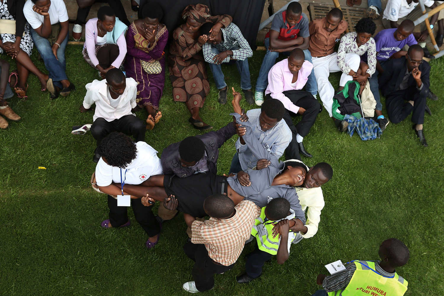 Apr. 7, 2014. Ushers carry a screaming and emotionally distraught woman out of Amahoro Stadium during the 20th anniversary commemoration of the 1994 genocide in Kigali, Rwanda.
