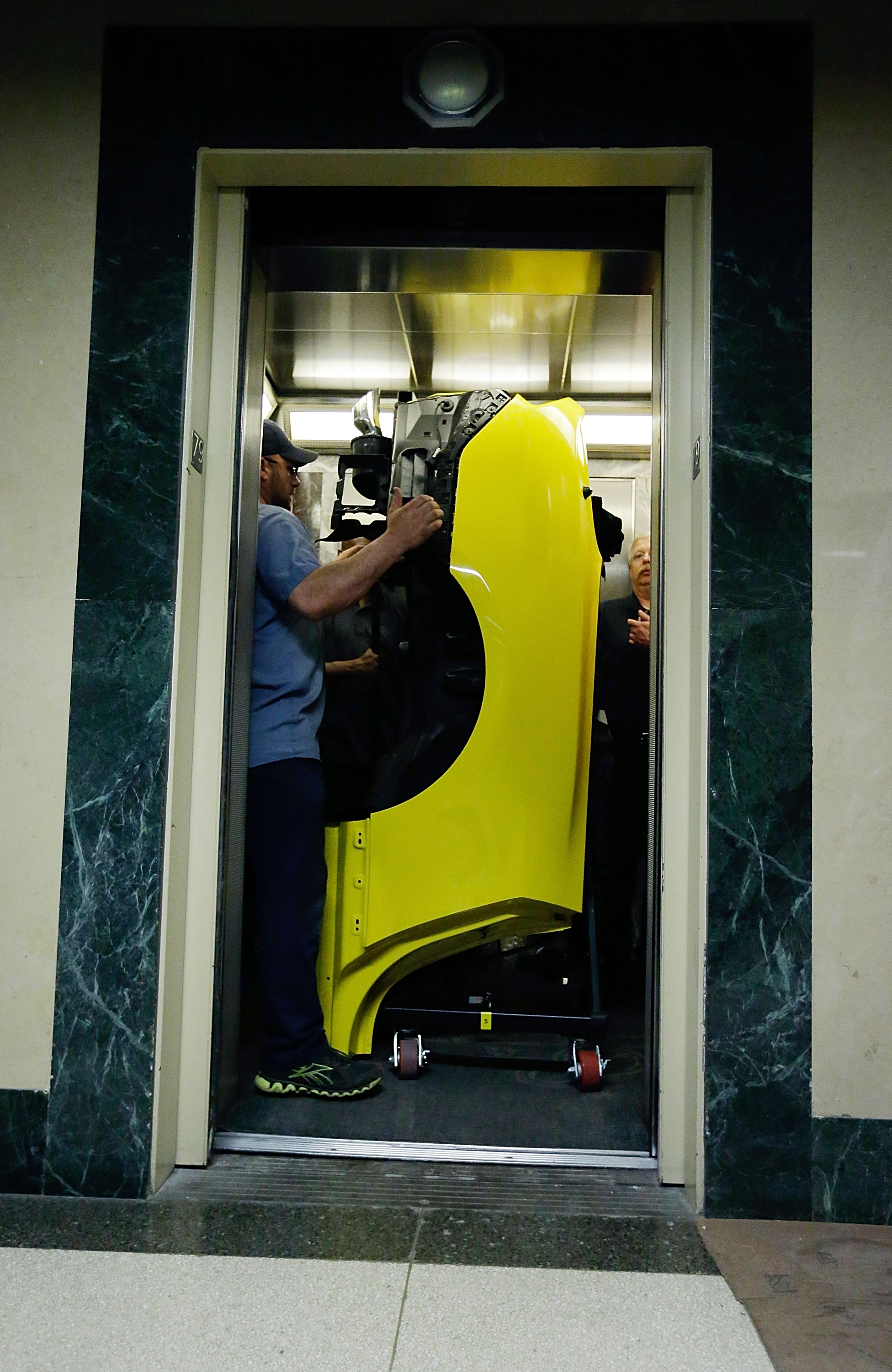 Workers load 2015 Ford Mustang components into the elevators.
