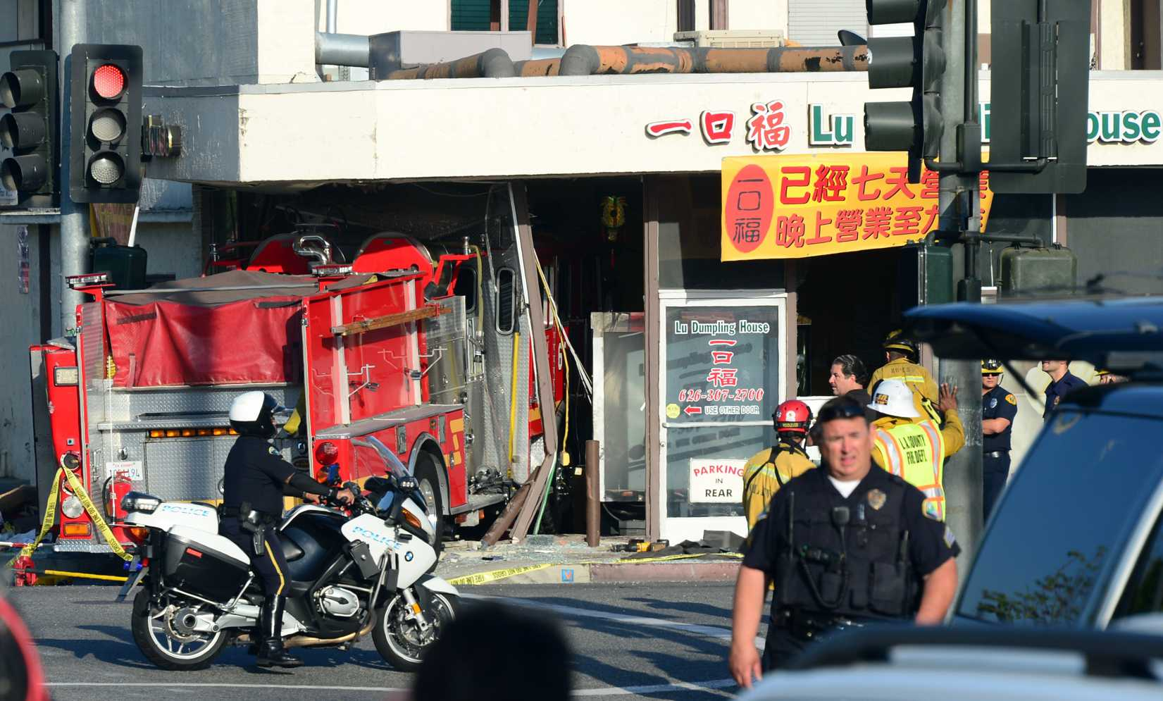 A motorcycle policeman arrives on the scene in Monterey Park, California on April 16, 2014, where two fire engines - one from the Monterey Park Fire department, another from the Alhambra Fire Department - chasing a fire crashed into each other with one barreling into a business, the Lu Dumpling House, leaving fifteen people injured.