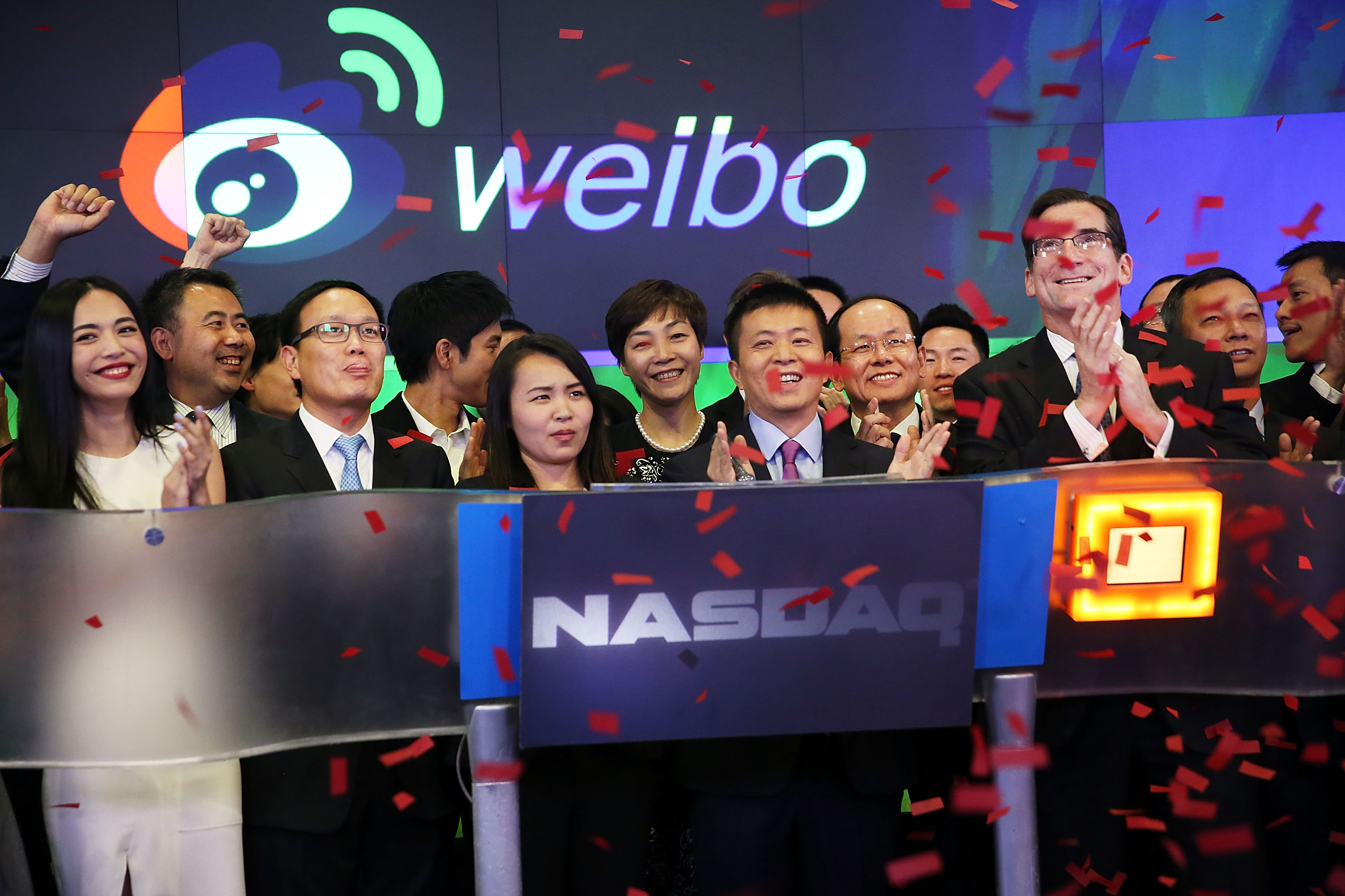 China's Weibo CEO Charles Chao (center) stands with Robert Greifeld, Nasdaq CEO, moments after Weibo began trading on the Nasdaq exchange under the ticker symbol WB on April 17, 2014 in New York City.