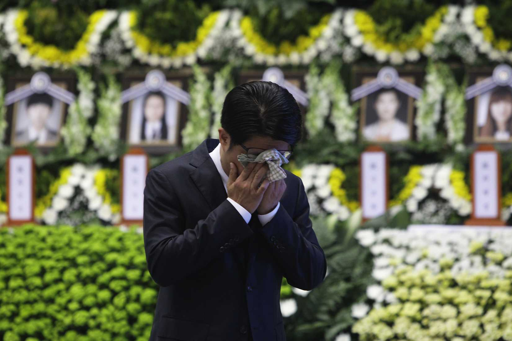 A man weeps after tribute at a group memorial altar for victims of sunken passengers ship at the Ansan Olympic Memorial Hall on April 23, 2014 in Ansan, South Korea.