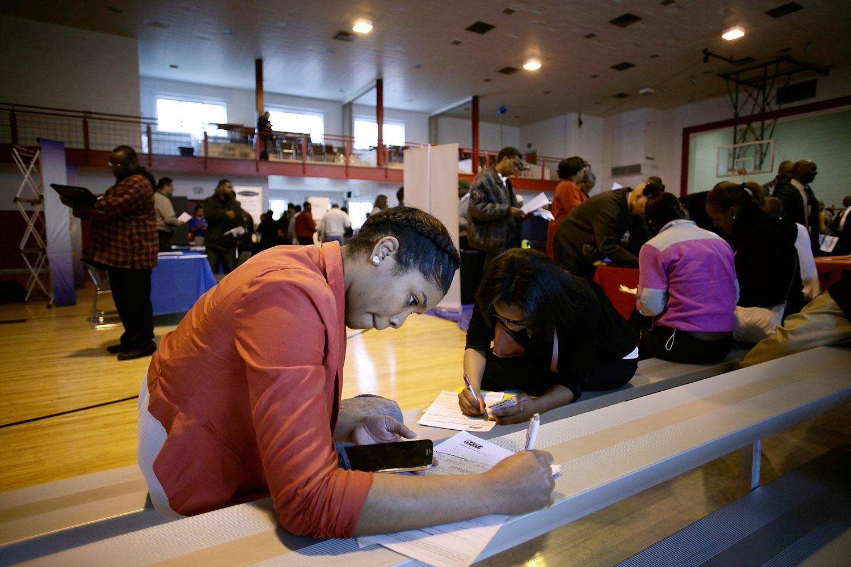 A woman seeking employment fills out an application at a job fair at the Matrix Center April 23, 2014 in Detroit, Mich.