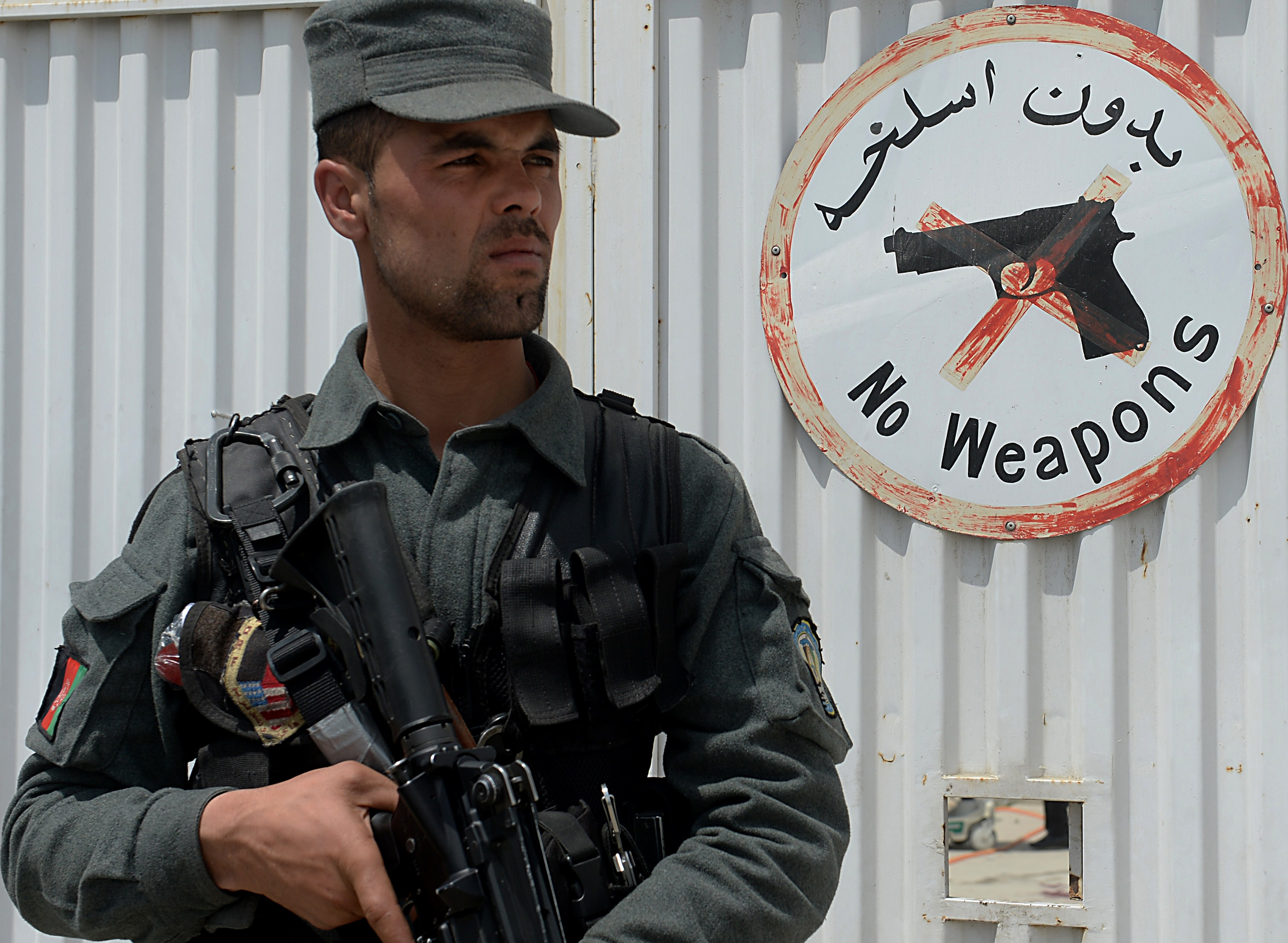 An Afghan policeman outside Kabul's Cure hospital, where another Afghan policeman killed three U.S. doctors Thursday.