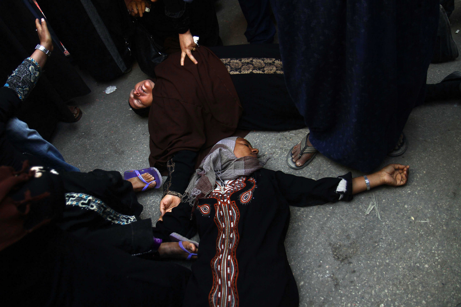 Apr. 28, 2014. Egyptian women overcome by emotion fall to the ground after a judge sentenced to death more than 680 alleged supporters of the country's ousted Islamist president over acts of violence and the murder of policemen in the latest mass trial in the southern city of Minya.