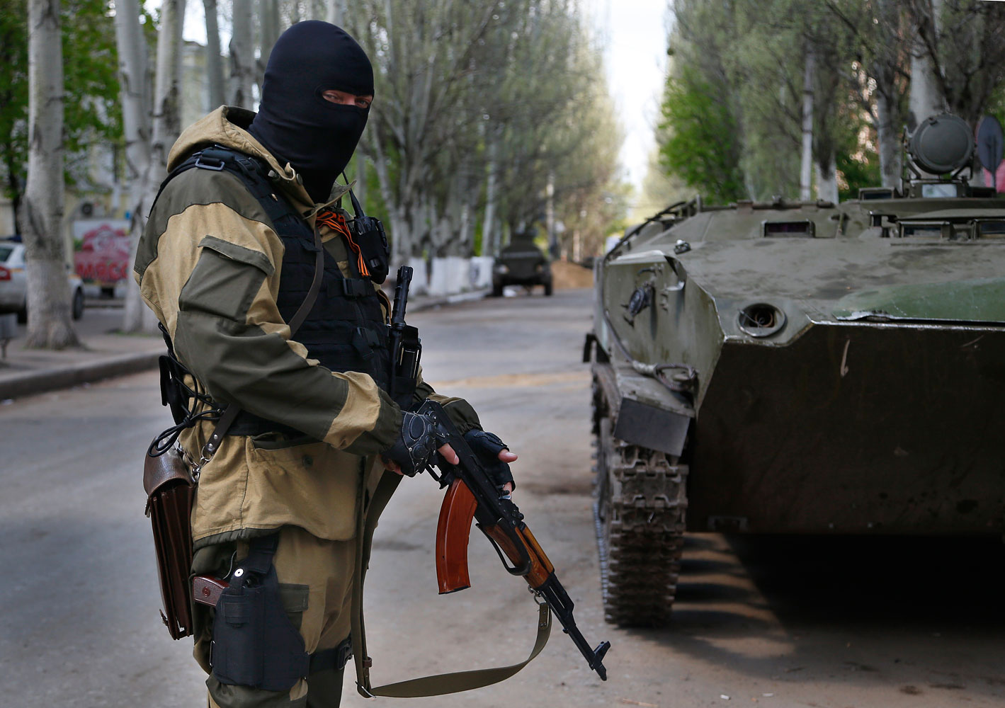 A pro-Russian masked gunman patrols a street  in the center of Slovyansk, eastern Ukraine, April 23, 2014.