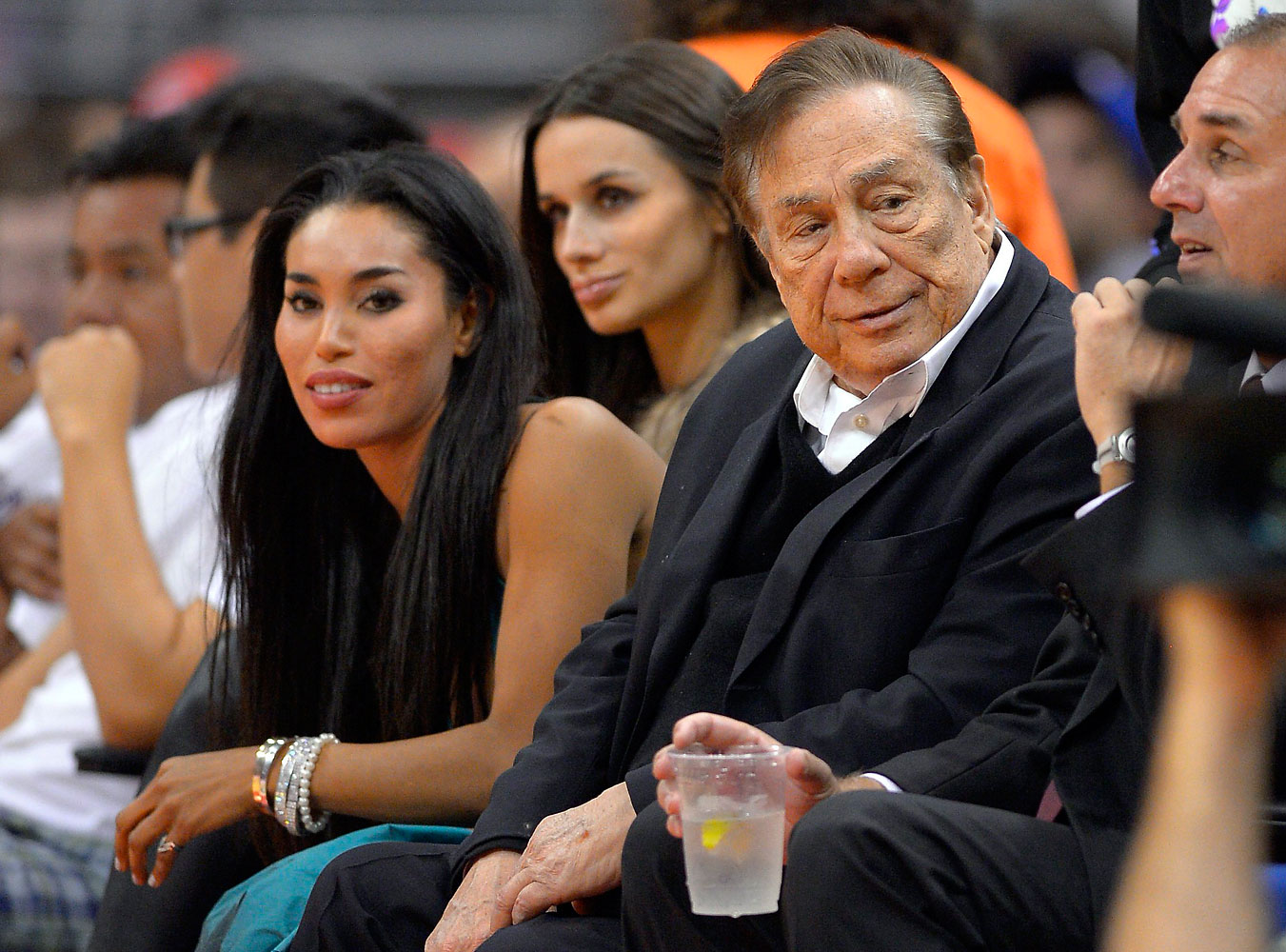 Los Angeles Clippers owner Donald Sterling and V. Stiviano watch the Clippers play the Sacramento Kings during an NBA game in Los Angeles on Oct. 25, 2013