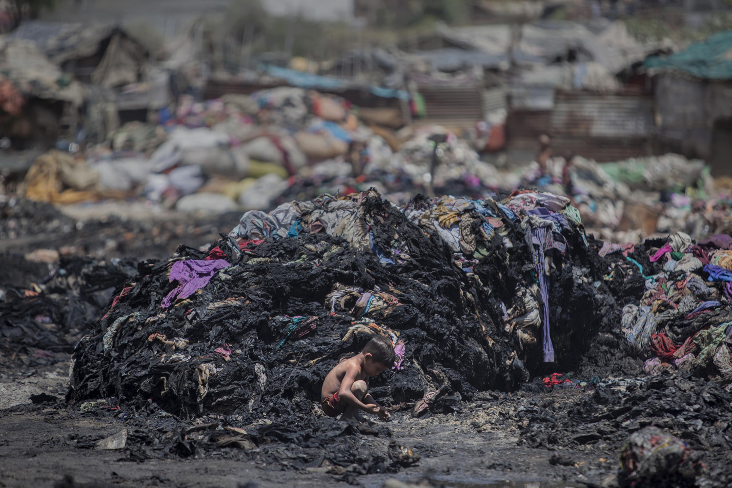 Apr. 28, 2014. An Indian boy looks for scrap metal amid charred debris after a fire at a slum in Ghaziabad, on the outskirts of New Delhi, India.