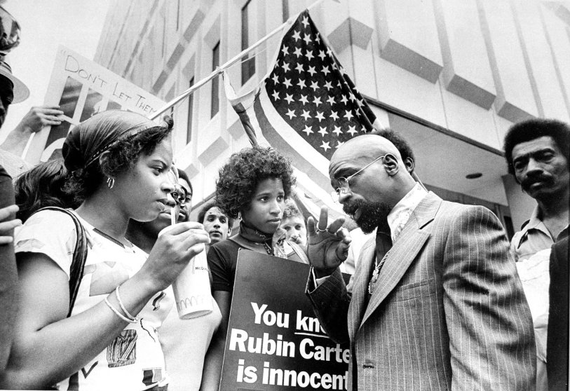 Boxer Rubin (Hurricane) Carter talks to people picketing on