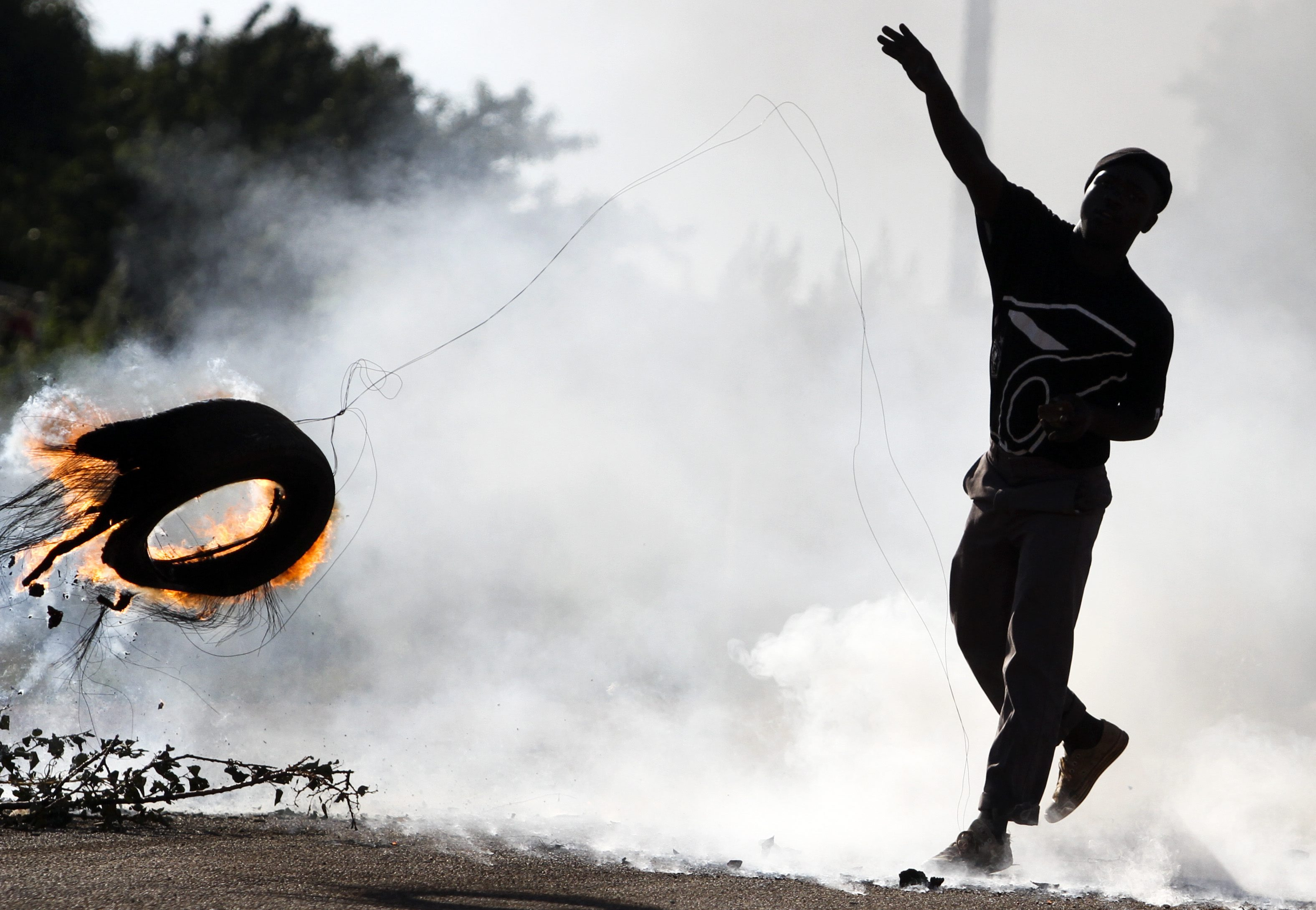 A South African man hurls a burning tire in Johannesburg during protests over squalid living conditions in 2010. Conditions for the poor are worsening around the world