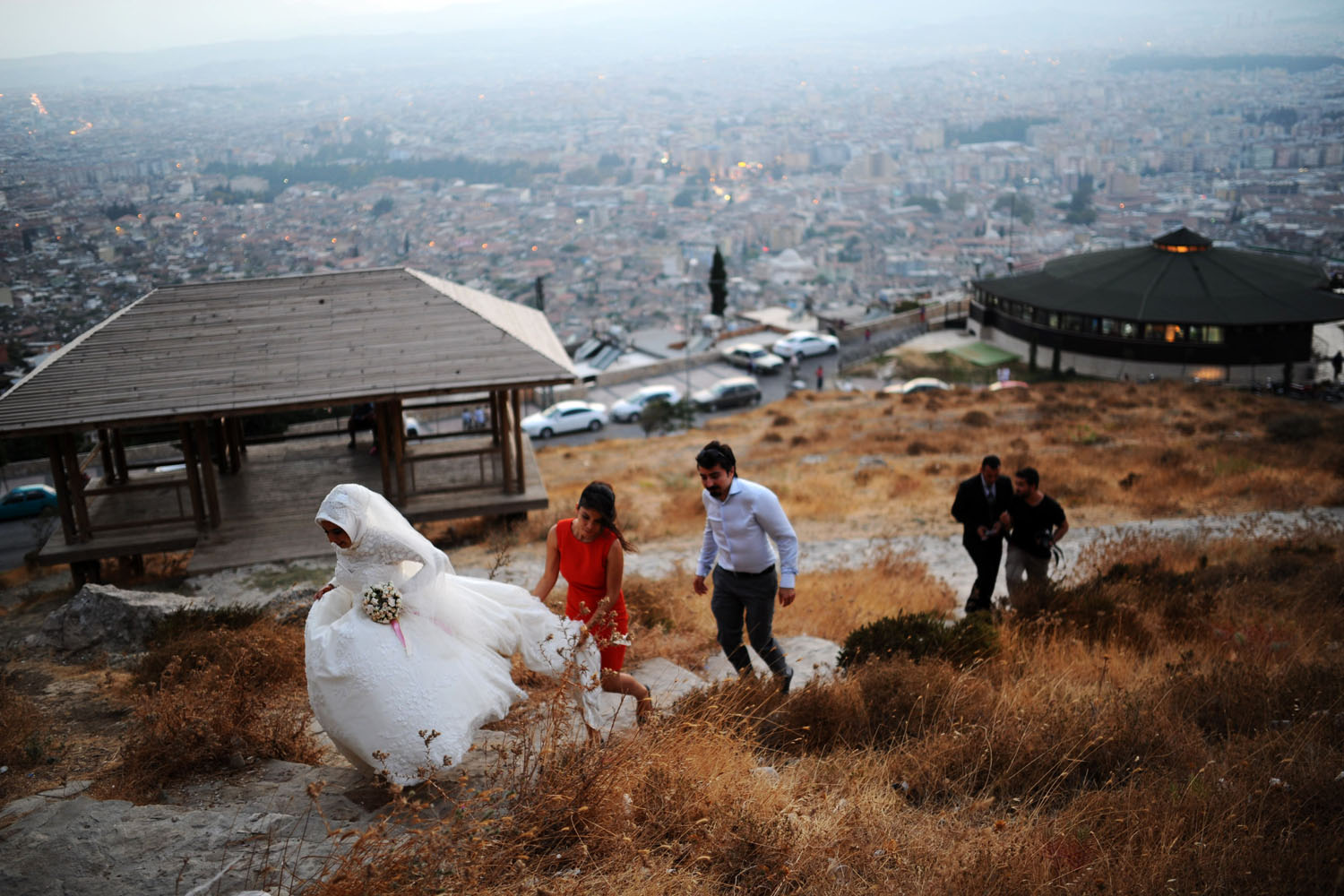 A newly married couple walks up a hill with a view of the city of Antakya, Turkey, Aug. 29, 2013.