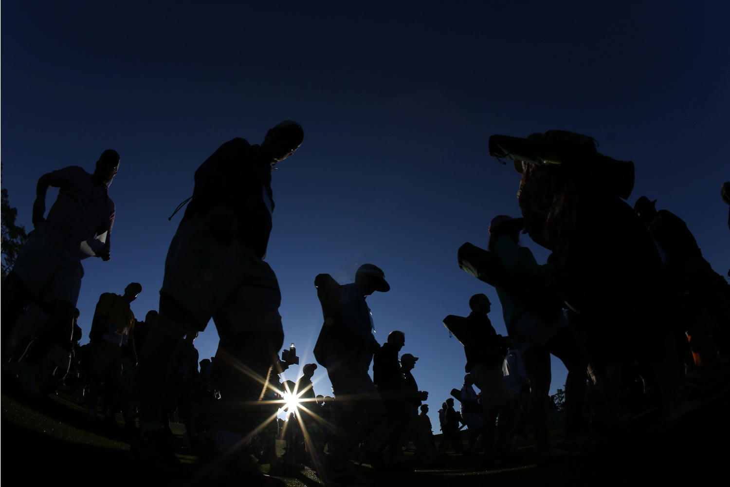 Apr. 10, 2014. Spectators make their way down the first fairway at sunrise for the first round of the Masters golf tournament in Augusta, Ga.