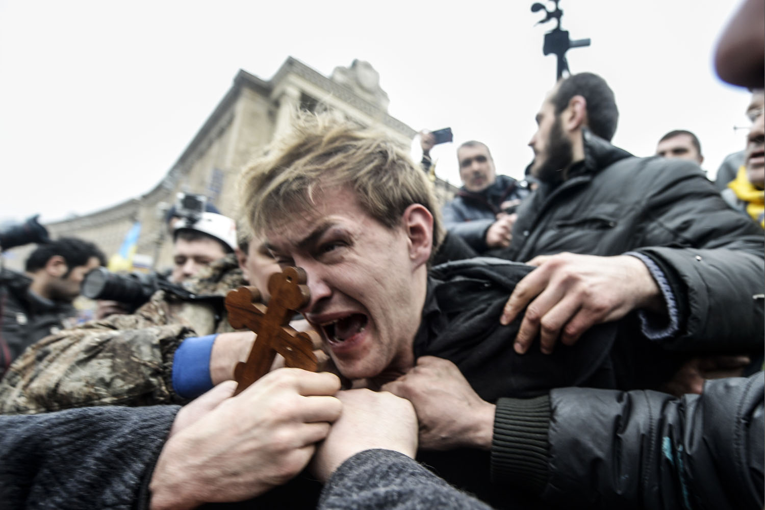 Center: An alleged sniper and member of the pro-government forces is beaten by anti-government protestors in Kiev, Ukraine, Feb. 22, 2014.