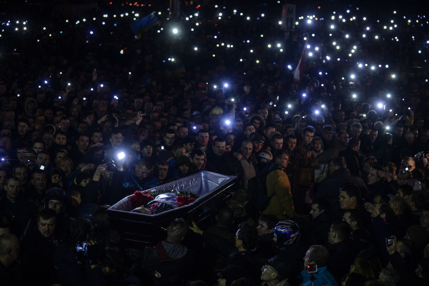 People carry a coffin of a man who was killed during recent clashes, as they gather at Independence Square on Feb. 22, 2014.