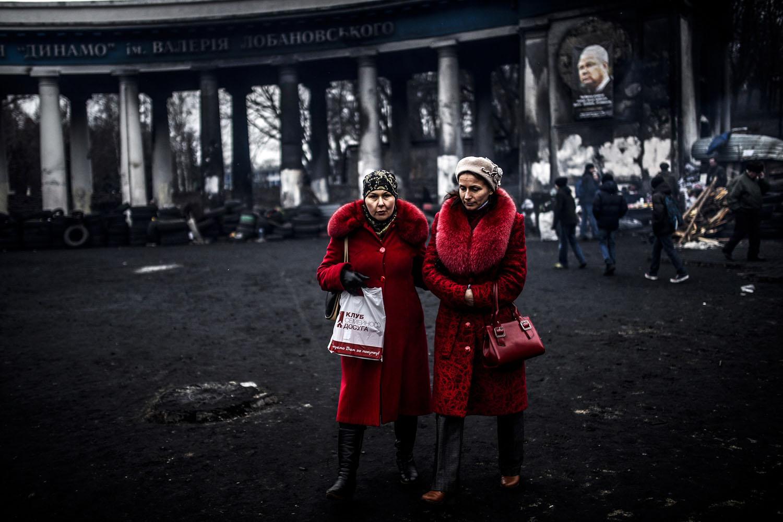 Women walk in front of the Dinamo Kiev's stadium in Kiev, Ukraine, Feb. 25, 2014.