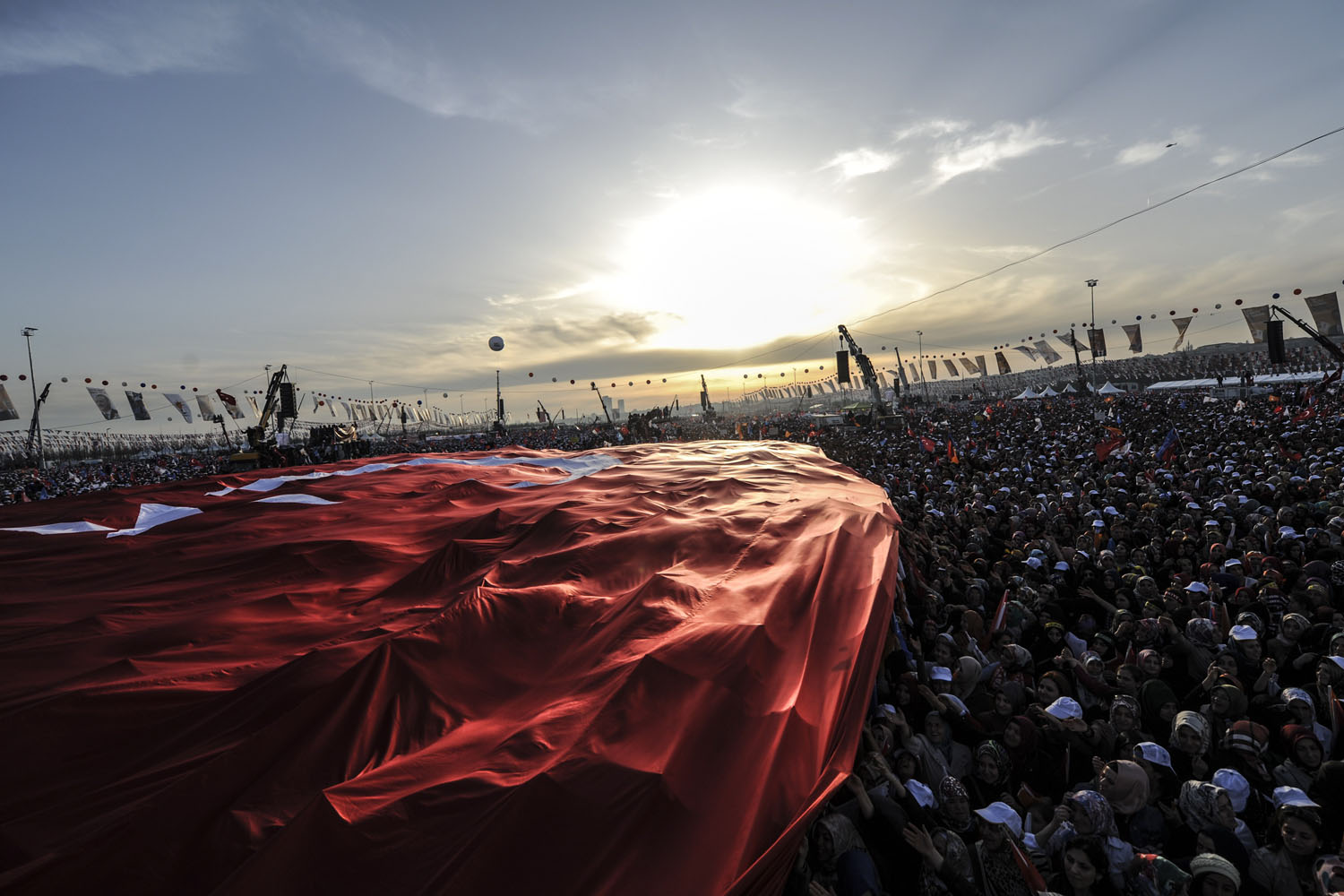 Supporters of Turkey's Prime Minister Tayyip Erdogan hold a giant Turkish flag during an election rally in Istanbul March 23, 2014.