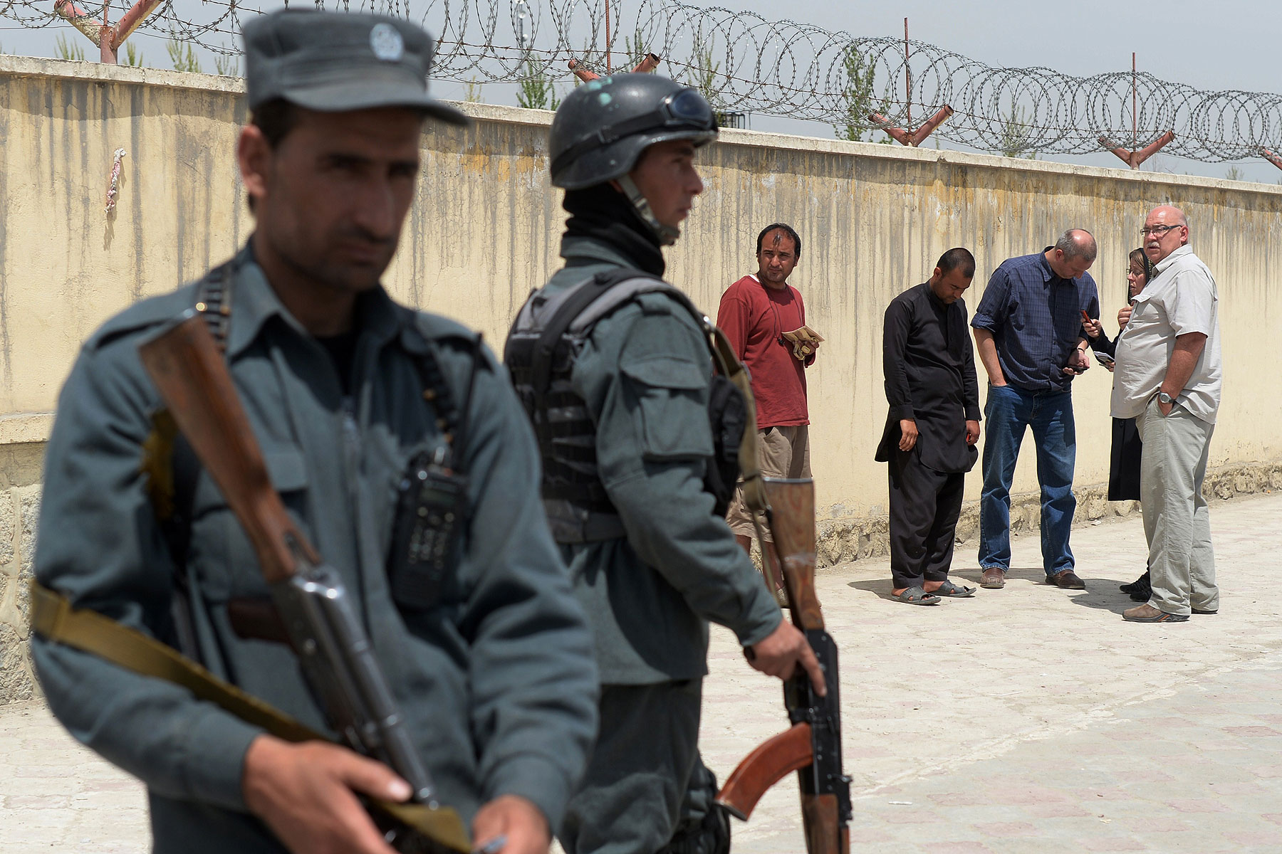 Afghan policemen keep watch as foreign nationals wait outside the Cure hospital in Kabul on April 24, 2014