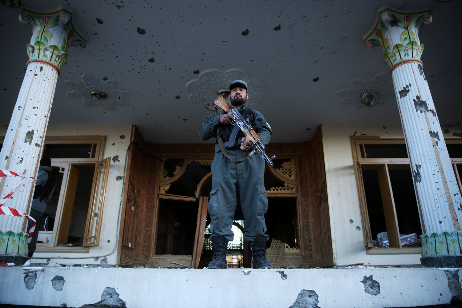 An Afghan policeman stands guard in front of an Independent Elections Commission (IEC) building after a gun battle between security forces and insurgents in Kabul, Afghanistan, Tuesday, March 25, 2014.