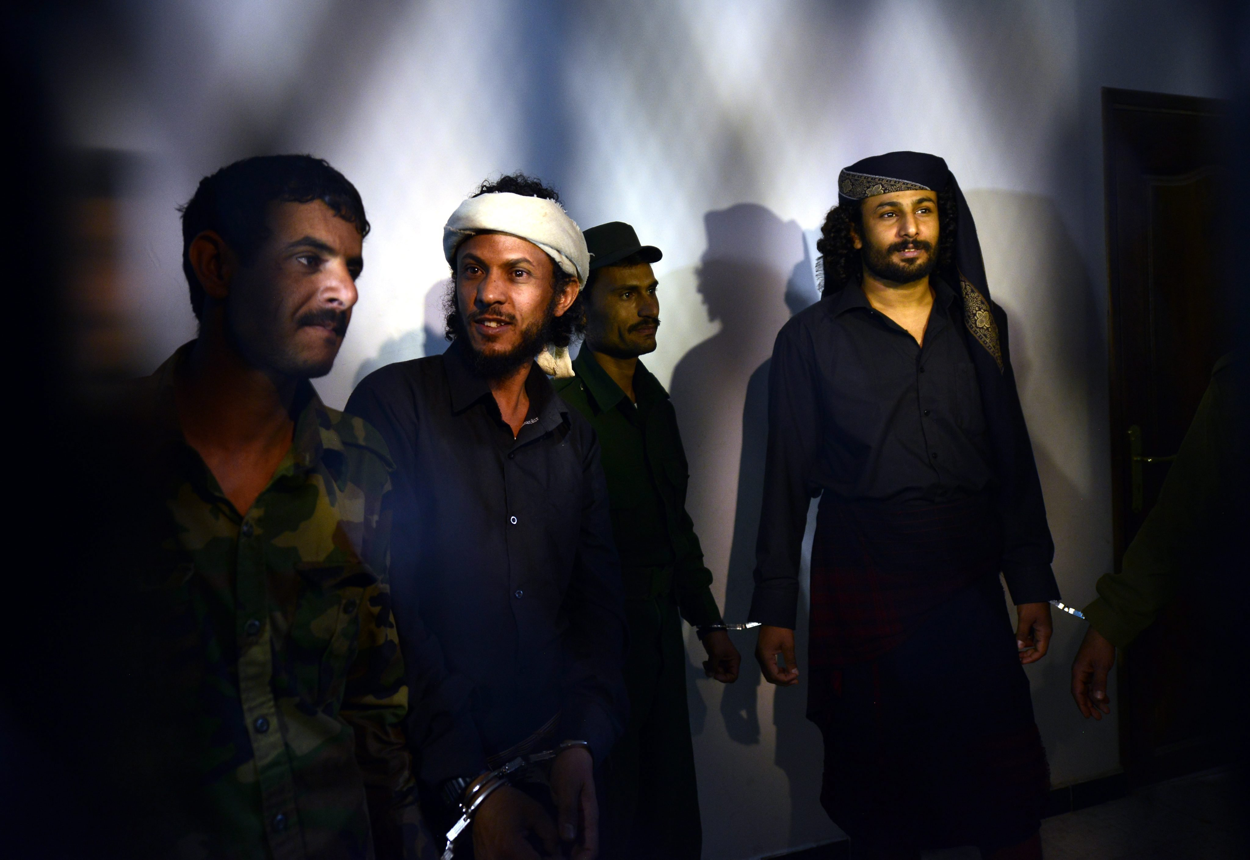 Al-Qaeda militants Sami Dayan, right, and Farhan al-Saadi, third from right, are escorted by soldiers during the sentence hearing at the state security court in Sana'a, Yemen on April  22, 2014.