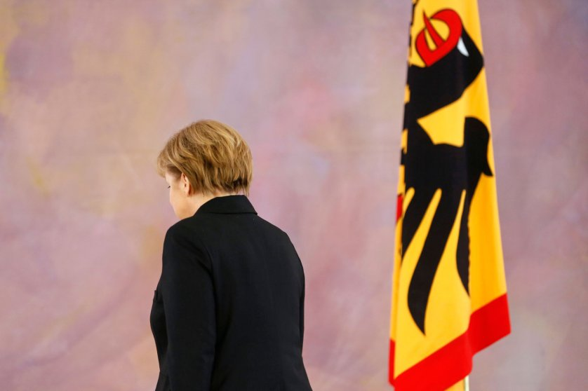 German President Joachim Gauck gives Chancellor Angela Merkel her new appointment papers during a ceremony in which Gauck appointed the new German government cabinet on December 17, 2013.