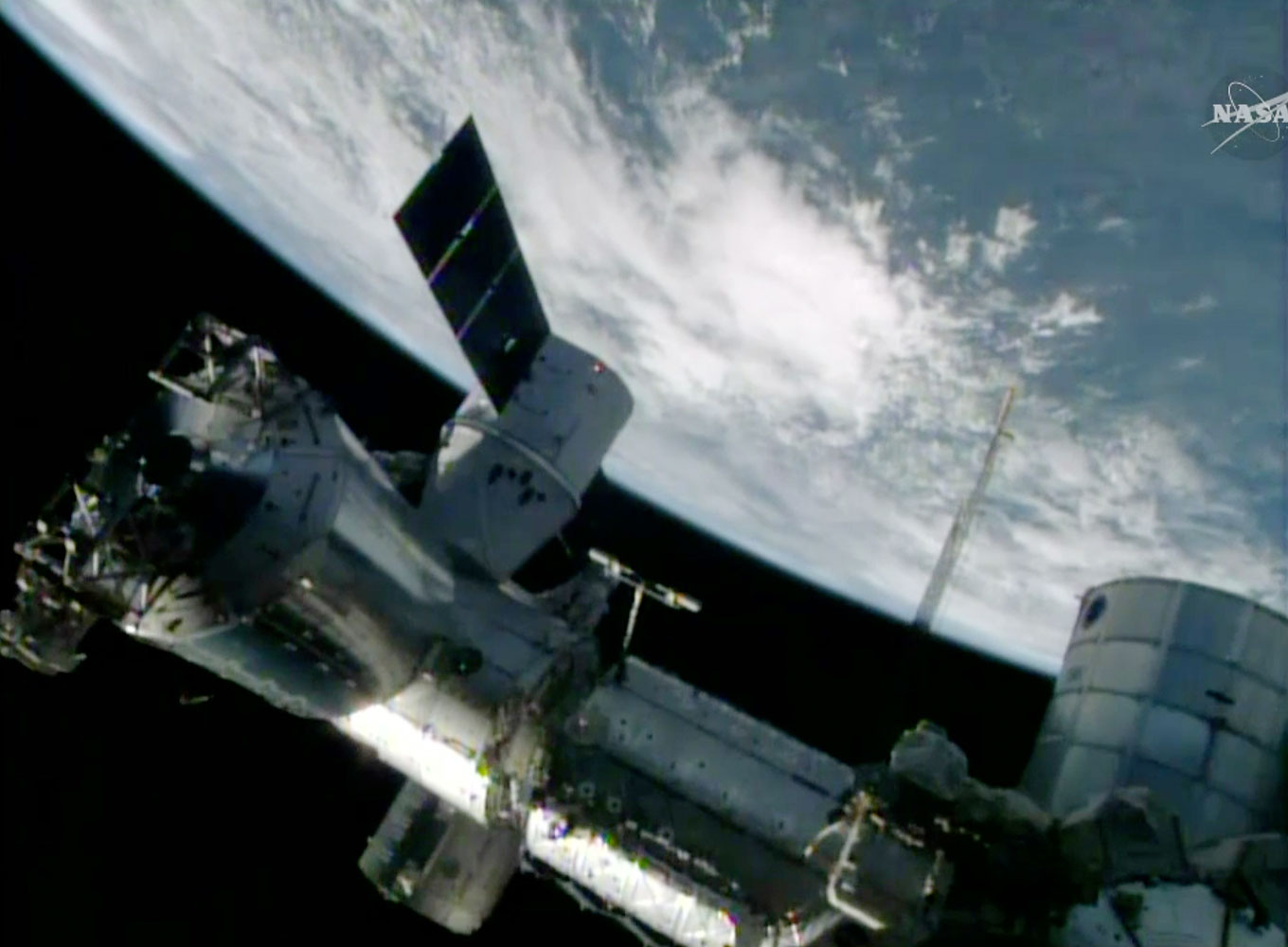 In this April 20, 2014 image made from a frame grabbed from NASA-TV, the SpaceX Dragon resupply capsule is birthed on to the International Space Station at 10:06 a.m. EDT.