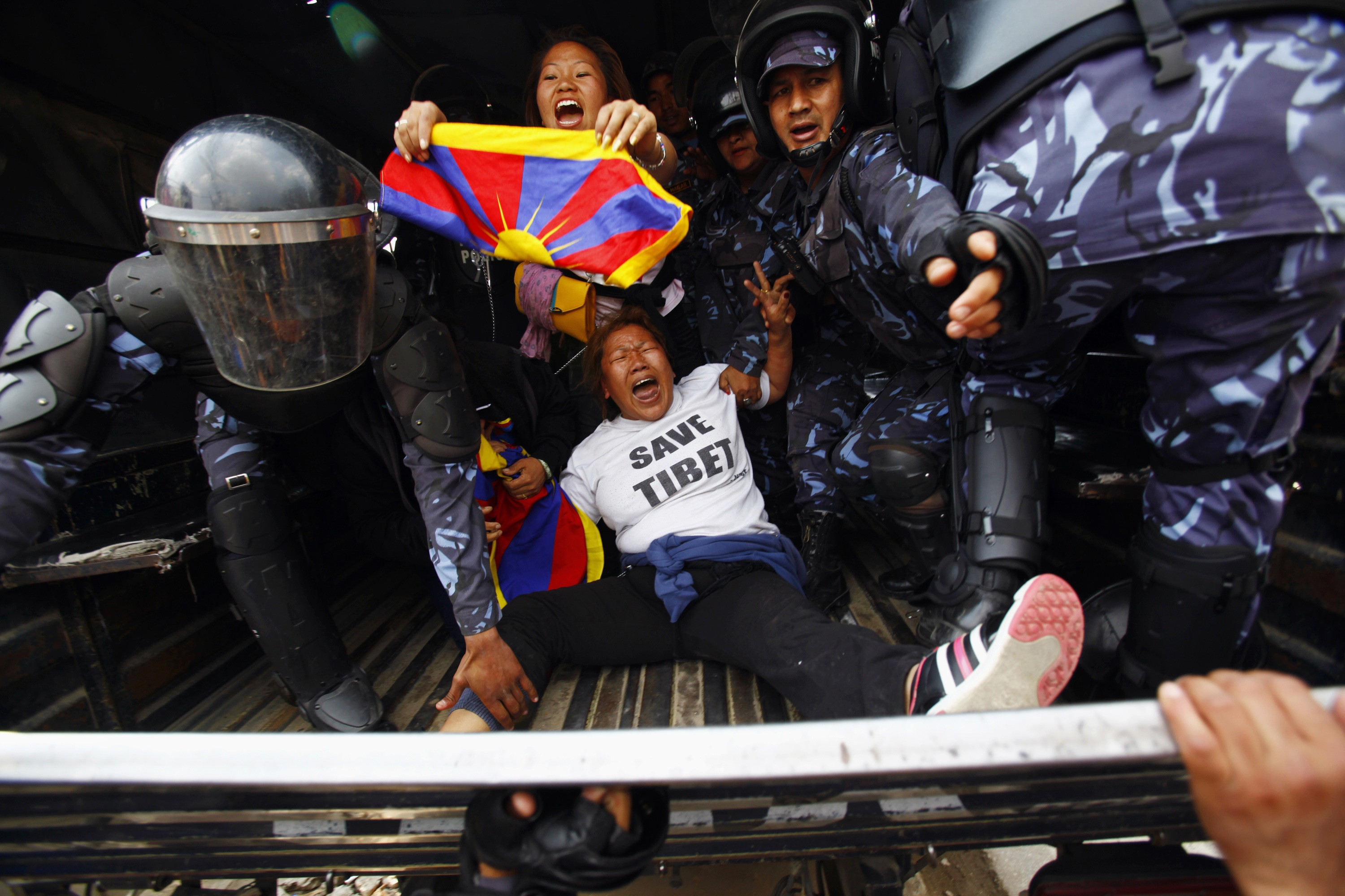 Nepali policemen detain exiled Tibetans participating in a protest outside the Chinese embassy in Kathmandu on March 10, 2014