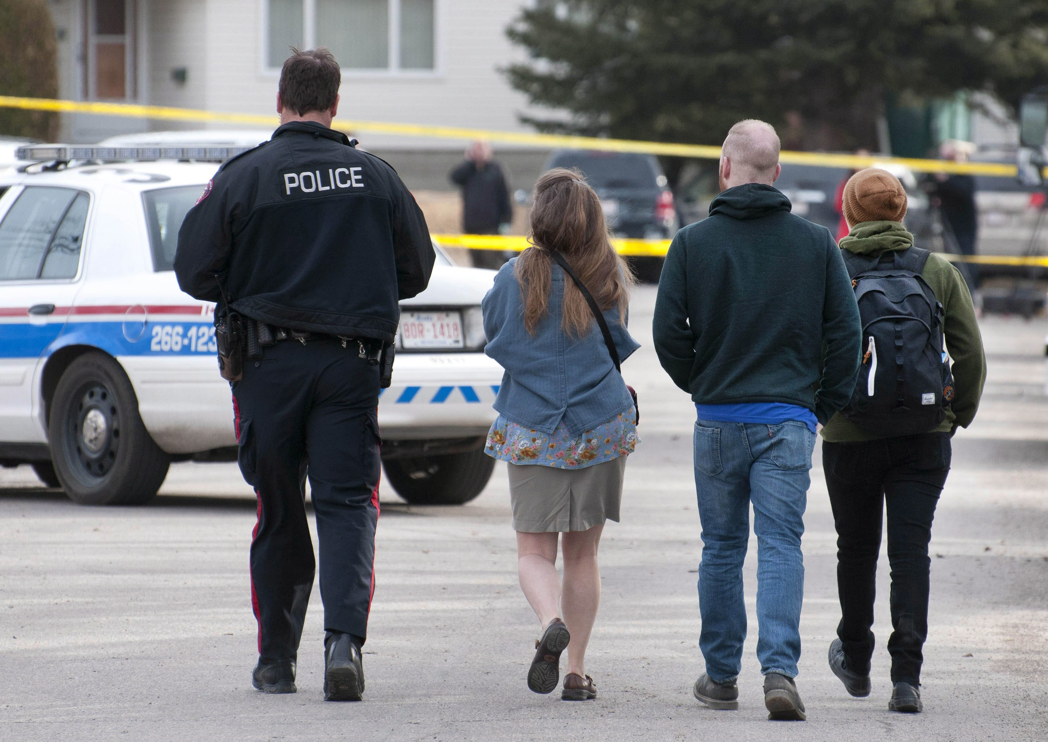 Calgary police lead away potential witnesses for statements regarding the multiple fatal stabbing in northwest Calgary, Canada, on April 15, 2014