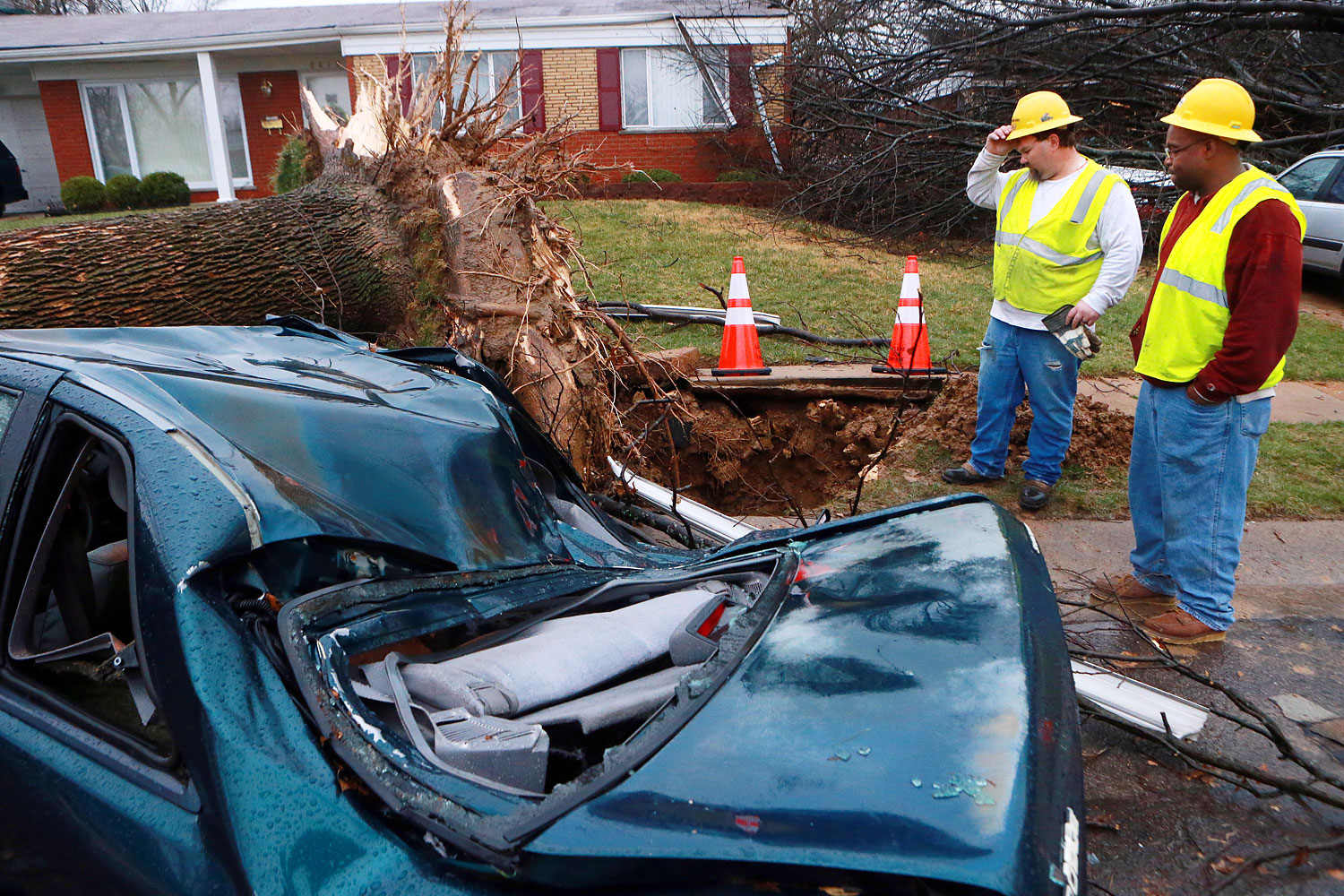 Jason Reidl, left, and Chris Thomas with Laclede Gas, look at a fallen tree that ruptured a gas main on Thursday April 3, 2014 in University City, Mo.