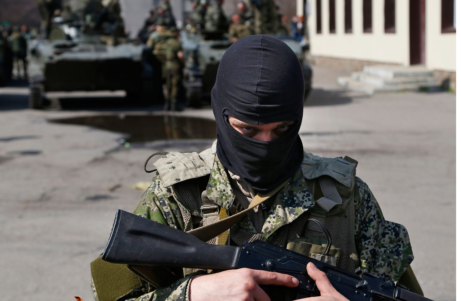 A masked gunman guards combat vehicles with Russian, Donetsk Republic and Ukrainian paratroopers, flags and gunmen on top, parked in downtown of Slovyansk on April 16, 2014.