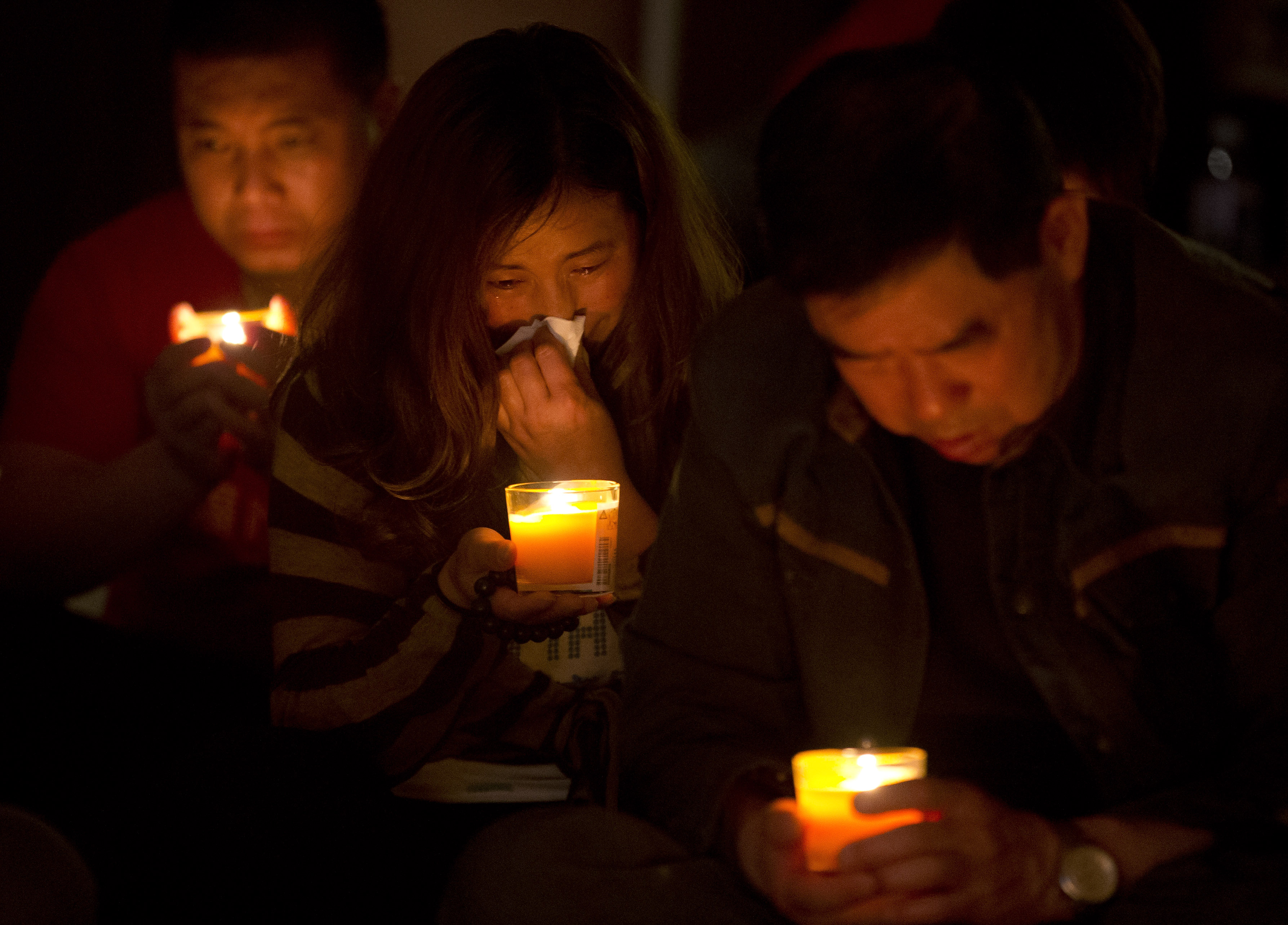 A woman cries as she and others attend a vigil for their loved ones, who were on the missing Malaysia Airlines Flight 370, at a hotel in Beijing on April 8, 2014