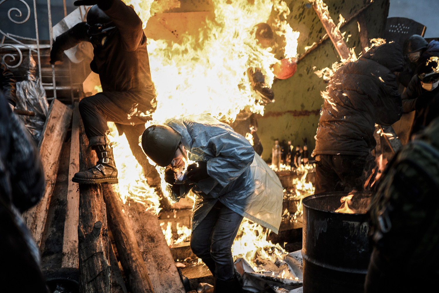 Protesters burn as they stand behind burning barricades during clashes with police in Kiev, Ukraine, Feb. 20, 2014.